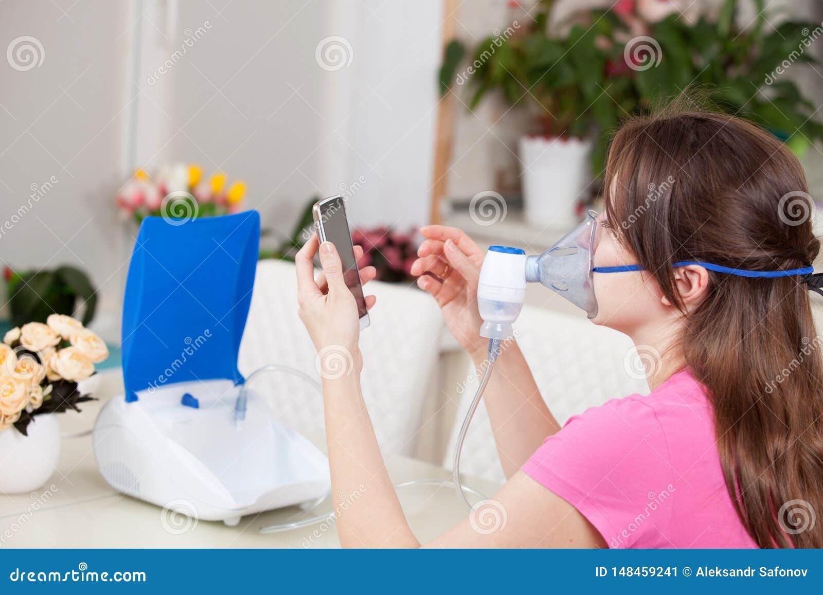 Mujer joven que hace la inhalaci?n con un nebulizador en casa marca el n?mero del doctor para una consulta