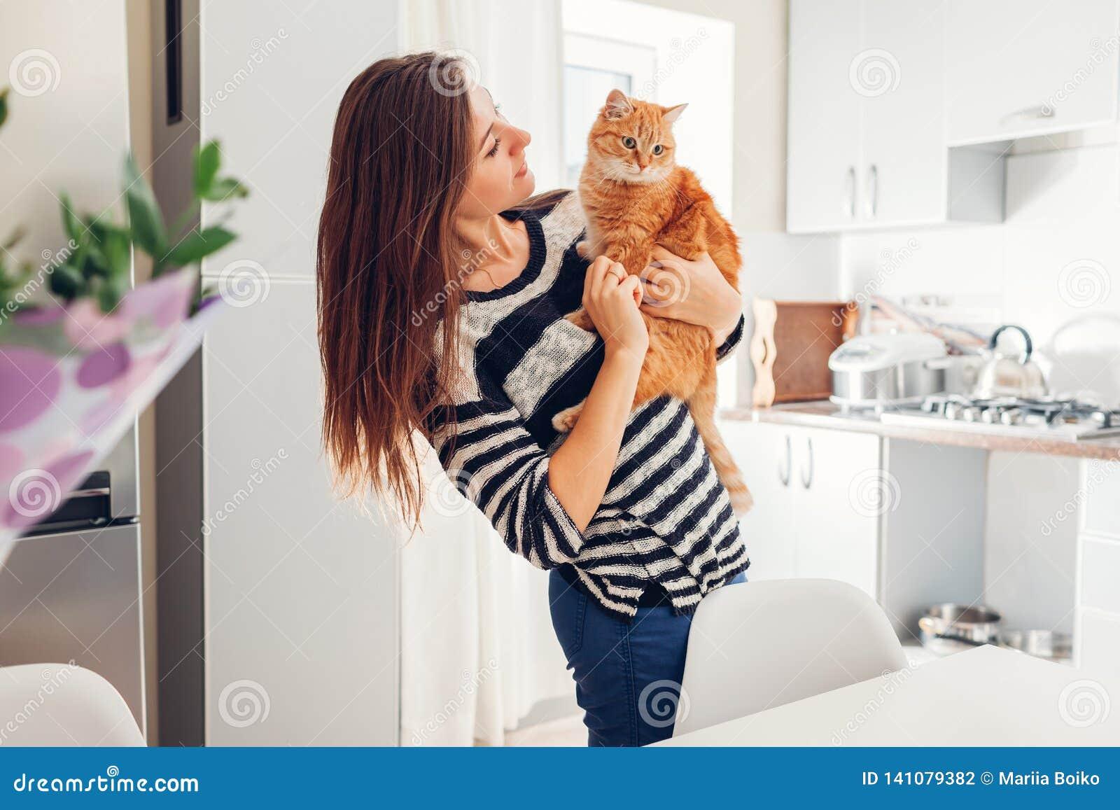 Mujer joven que juega con el gato en cocina en casa Muchacha que sostiene y que abraza el gato del jengibre