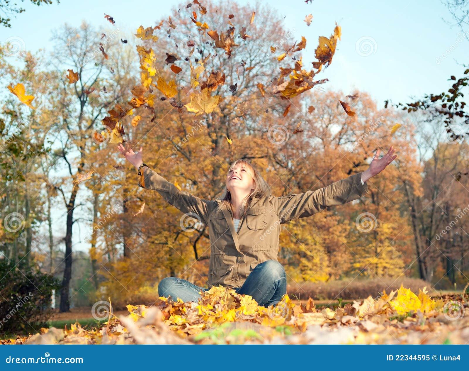 Mujer joven que juega con las hojas de otoño