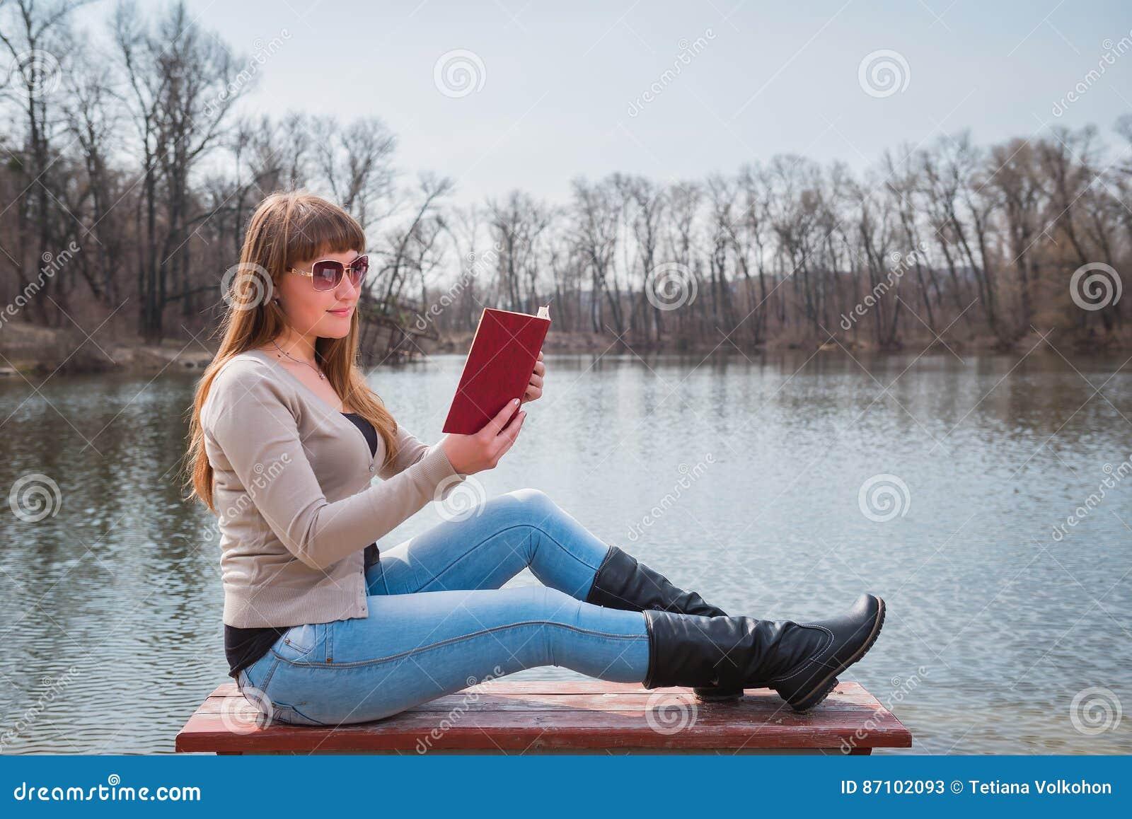 Mujer joven que lee el libro al aire libre en gafas de sol, forma de vida diaria, río en el fondo, primavera, día soleado