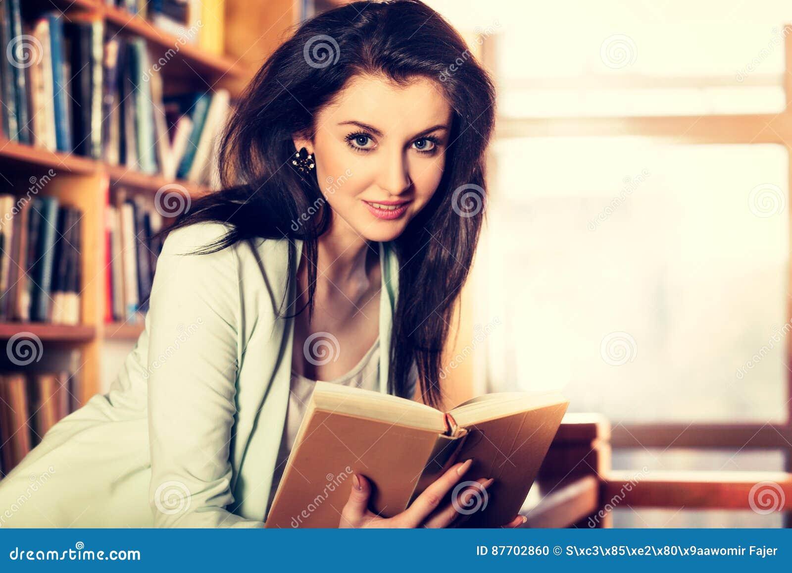Mujer joven que lee un libro delante de los estantes