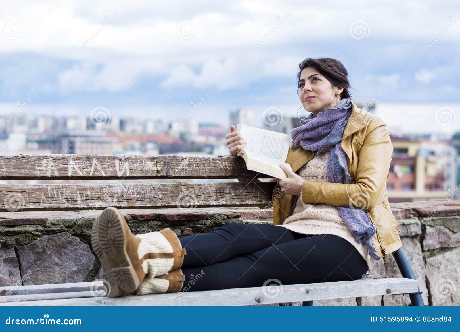 336f21910 Mujer Joven Que Lee Un Libro En Un Fondo Del Paisaje Urbano Foto de ...