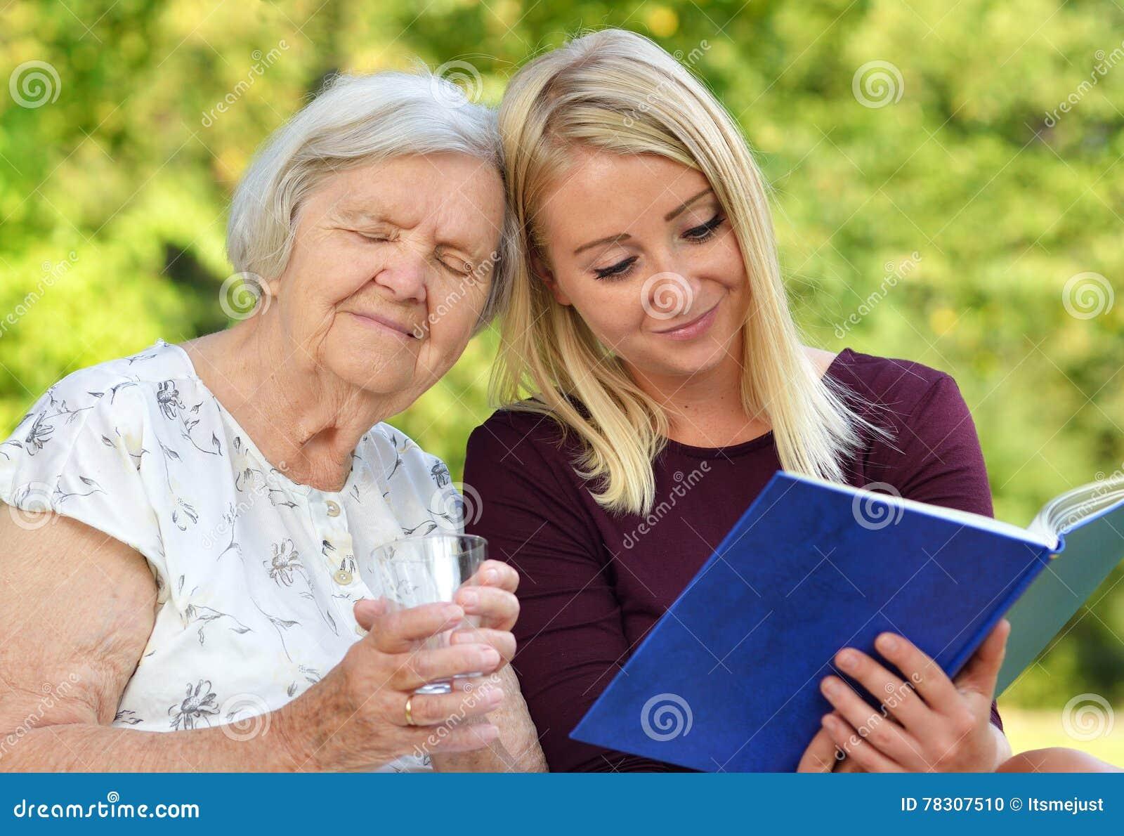Mujer joven que lee a una mujer de los ancianos del libro