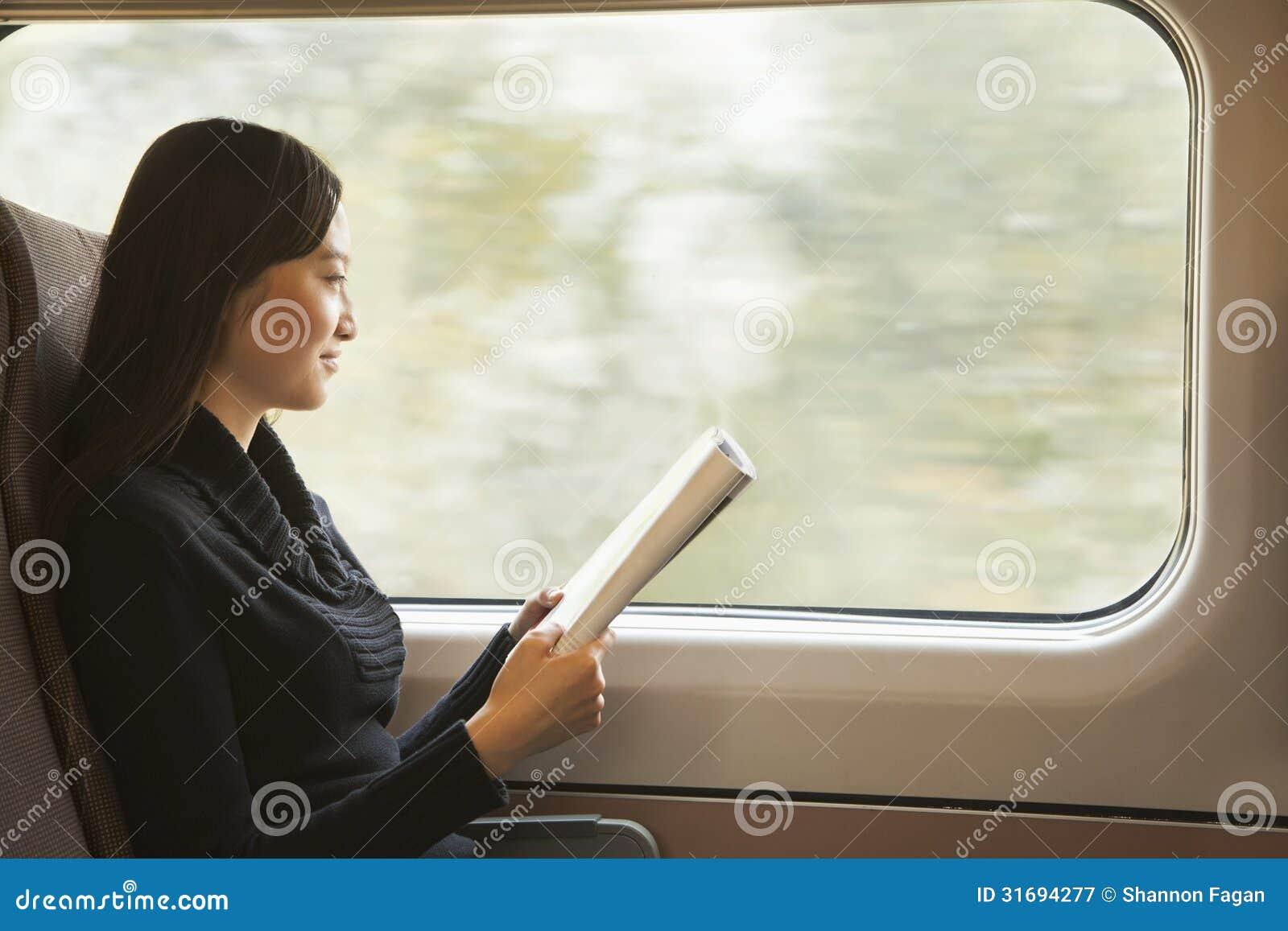 Mujer joven que lee una revista mientras que monta el tren