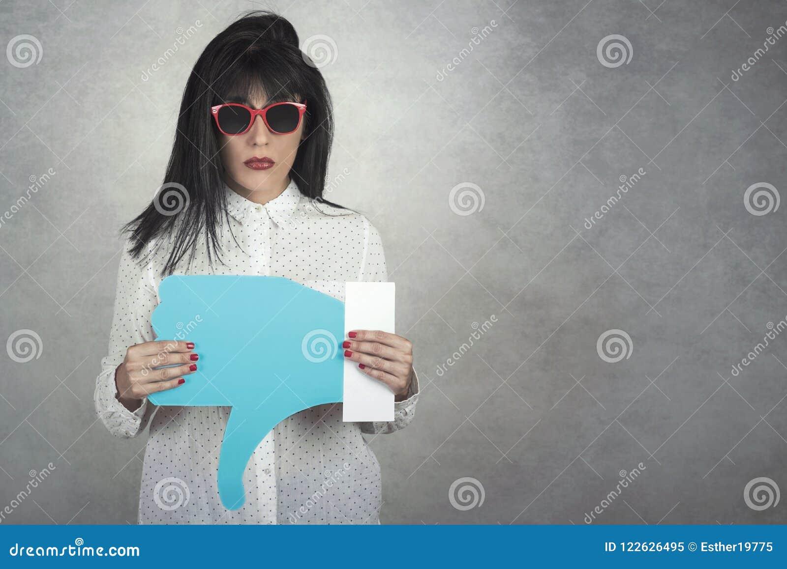 Mujer joven que lleva a cabo un icono de la aversión