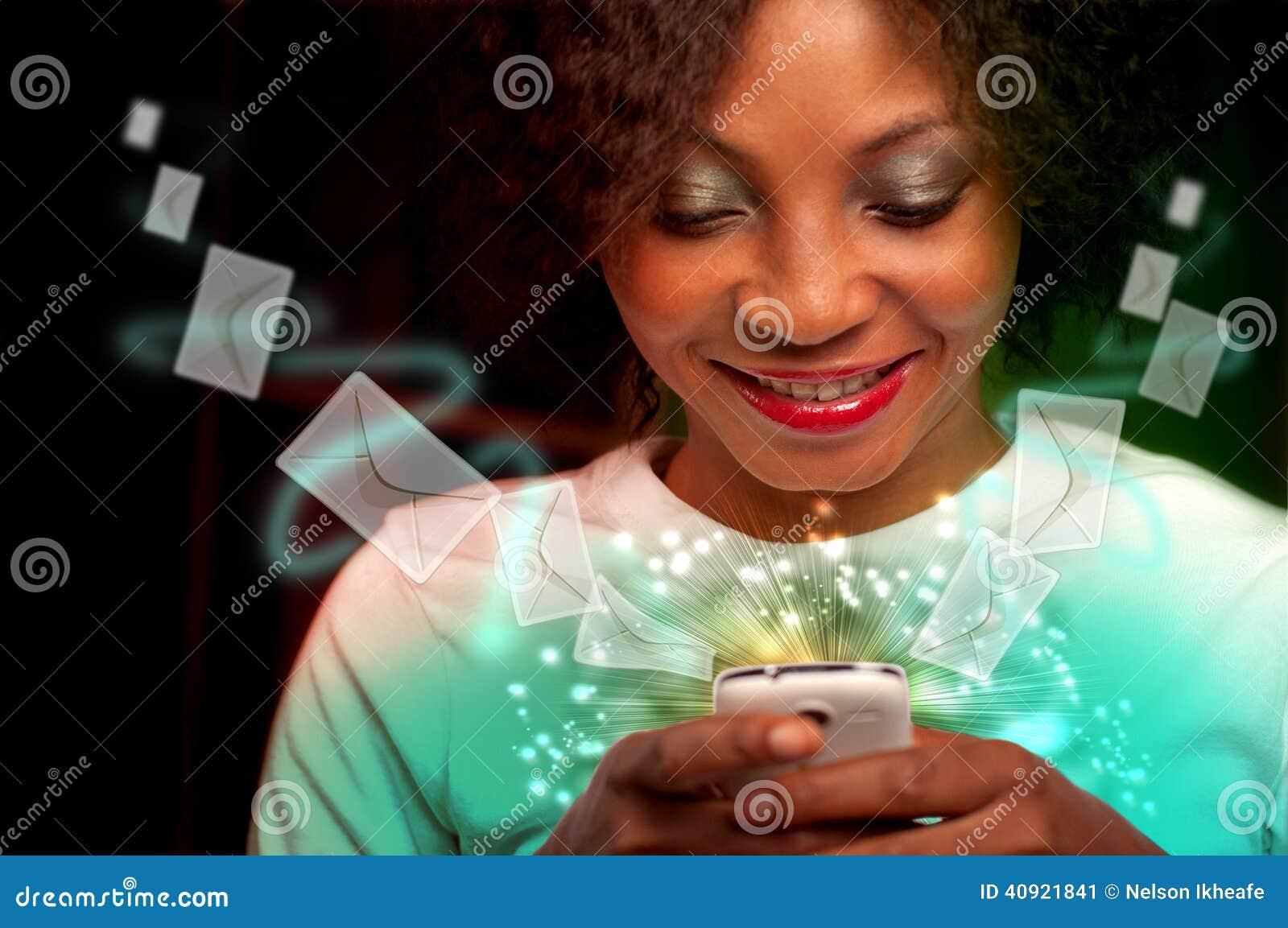 Mujer joven que manda un SMS en el teléfono móvil