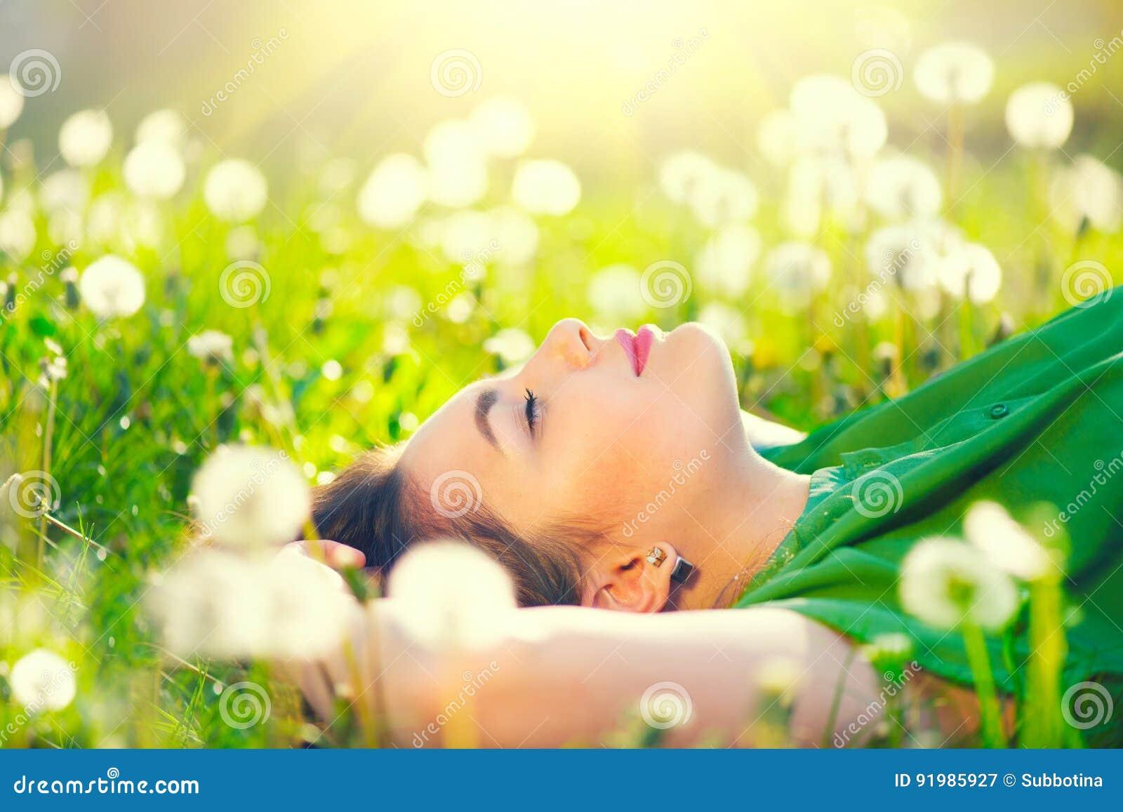 Mujer joven que miente en el campo en hierba verde y dientes de león