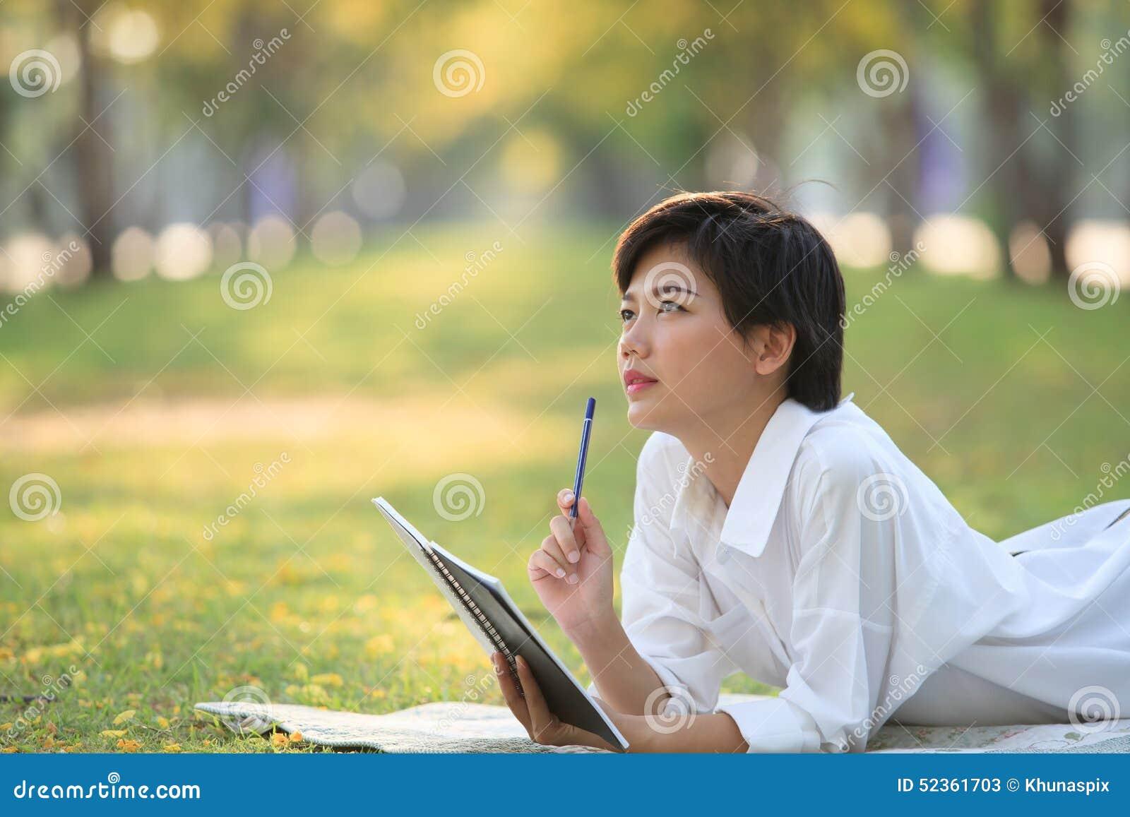 Mujer joven que miente en parque de la hierba verde con el lápiz y el cuaderno
