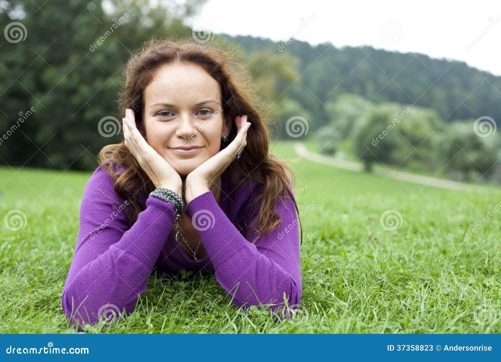 Mujer joven que miente en un césped verde
