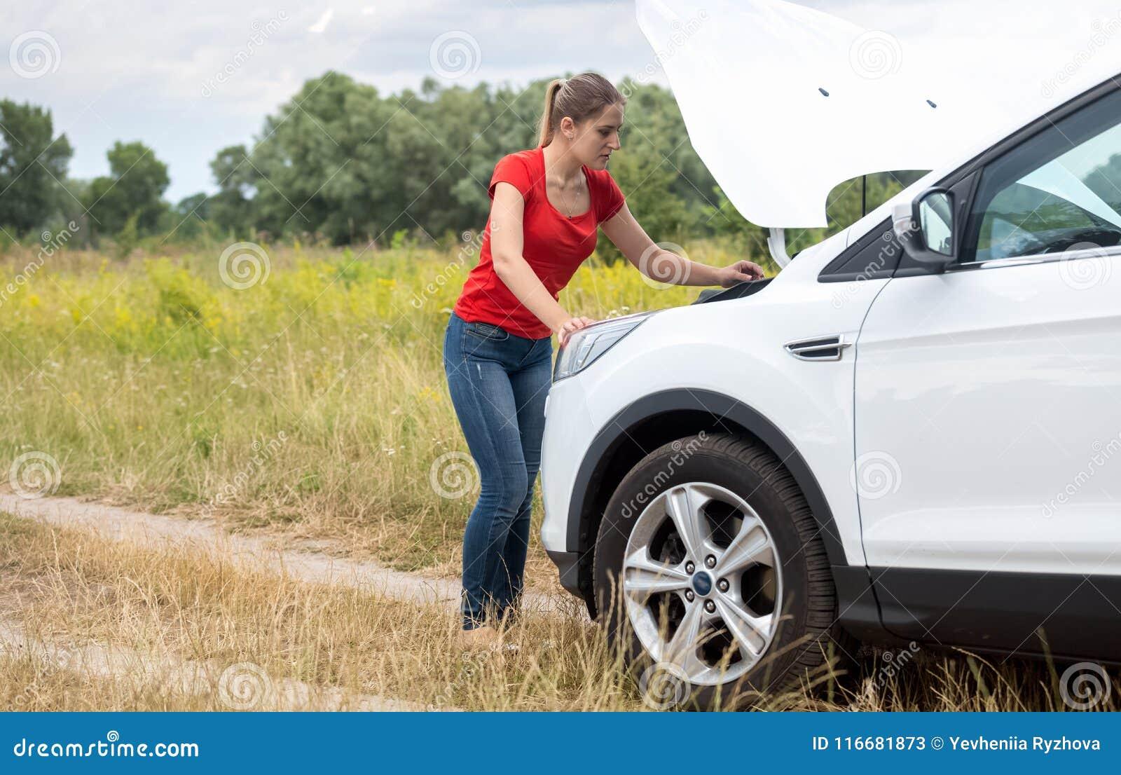 Mujer joven que mira debajo de la capilla del coche quebrado y que intenta fijarla