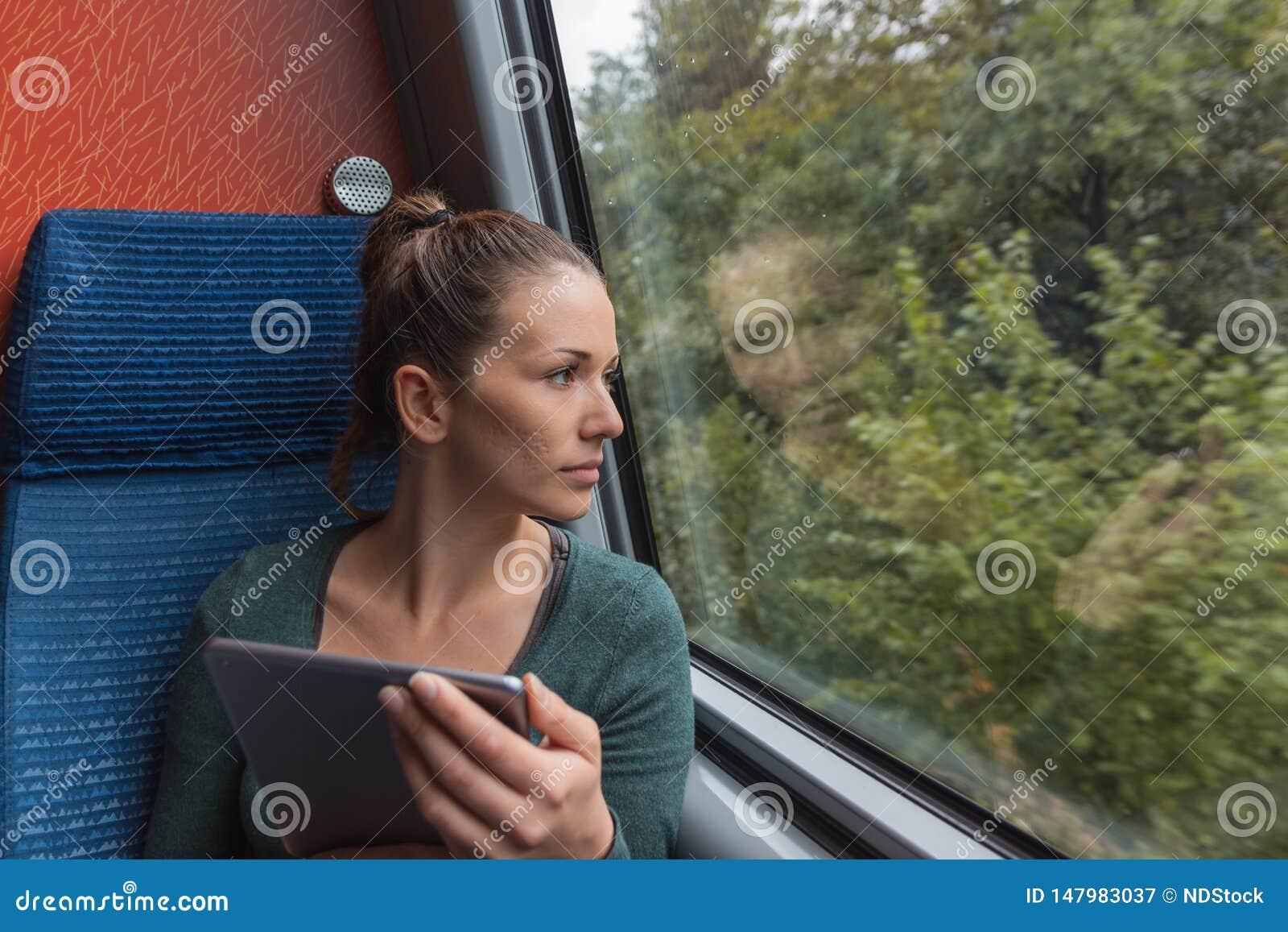 Mujer joven que mira fuera de la ventana y que usa una tableta para estudiar mientras que viaja en tren