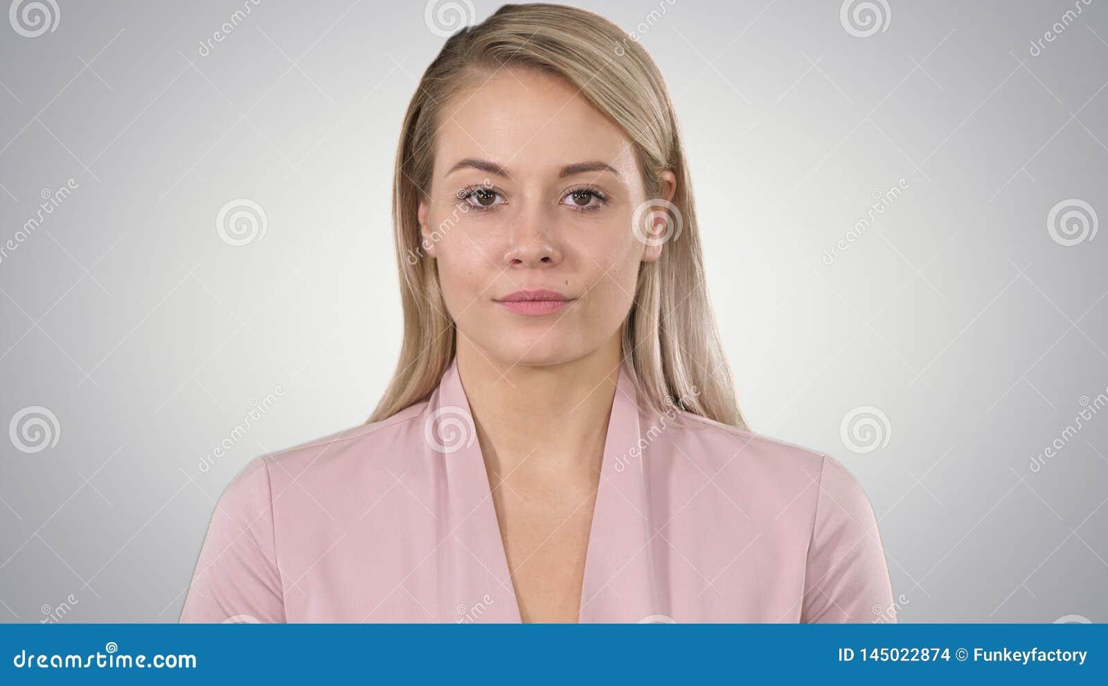 Mujer joven que mira a la c?mara y que escucha en fondo de la pendiente