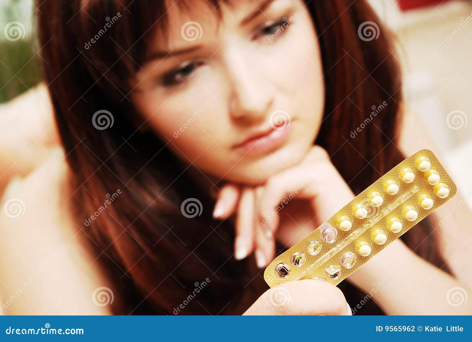 Mujer joven que mira sus píldoras anticonceptivas