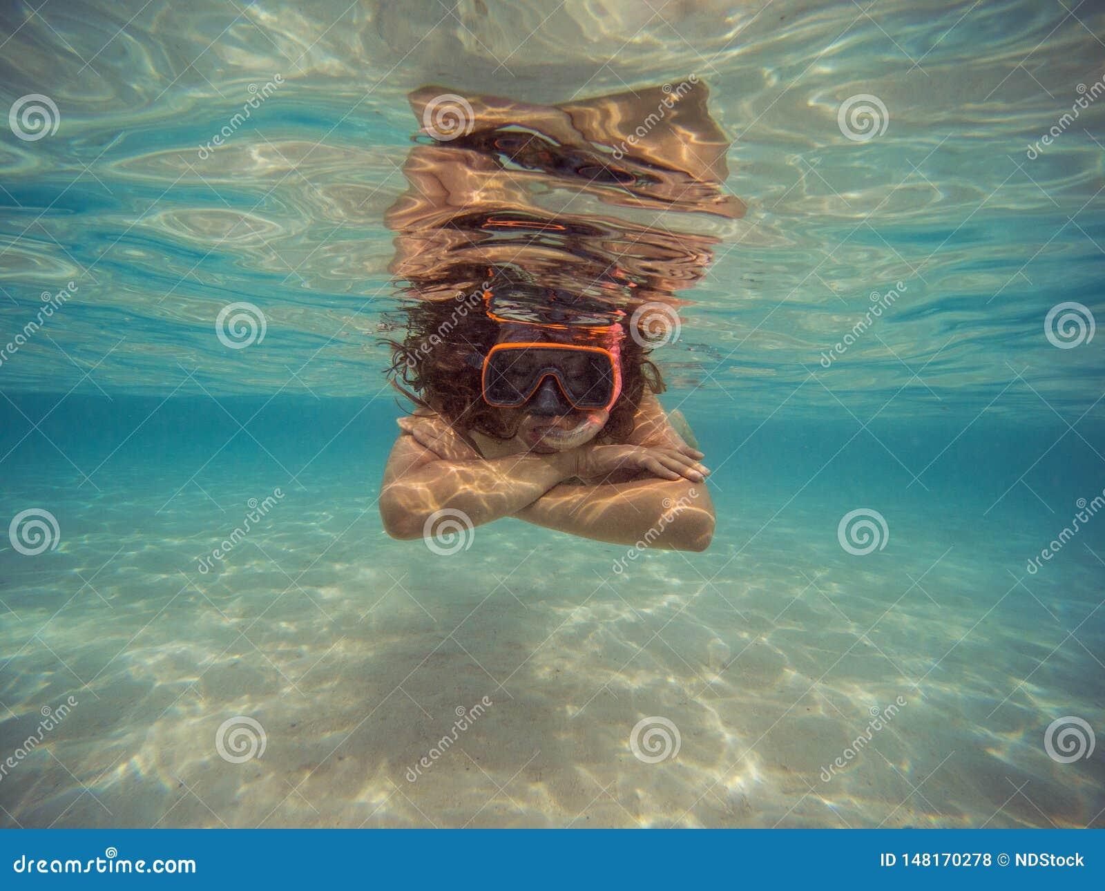 Mujer joven que nada y que bucea con la m?scara y las aletas en agua azul clara