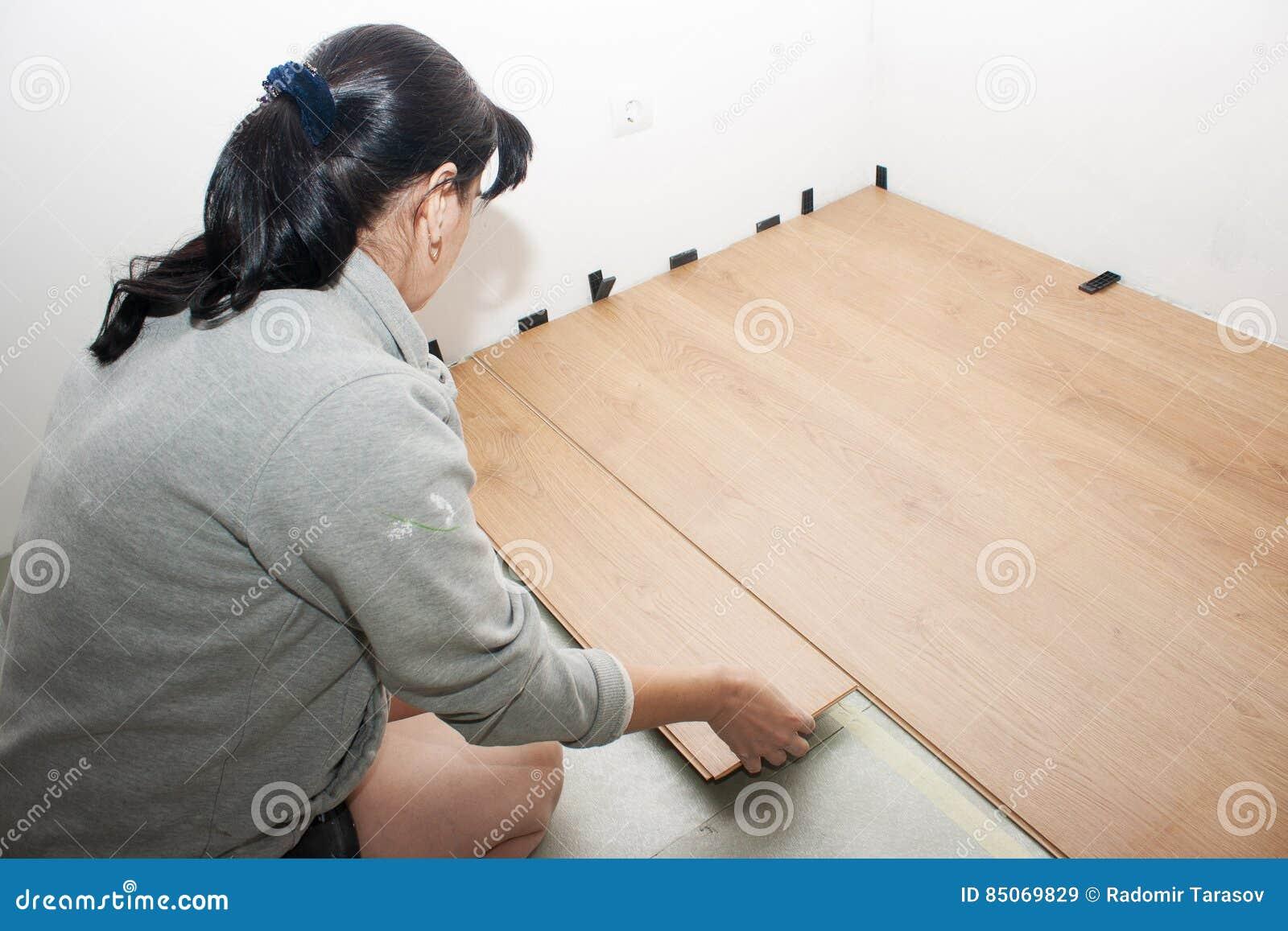 Mujer joven que pone el suelo laminado