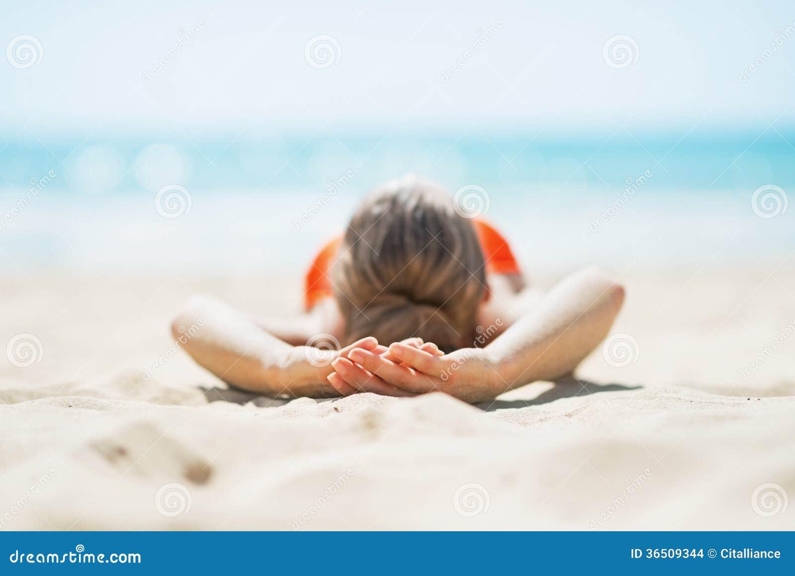 Mujer joven que pone en la playa. vista posterior