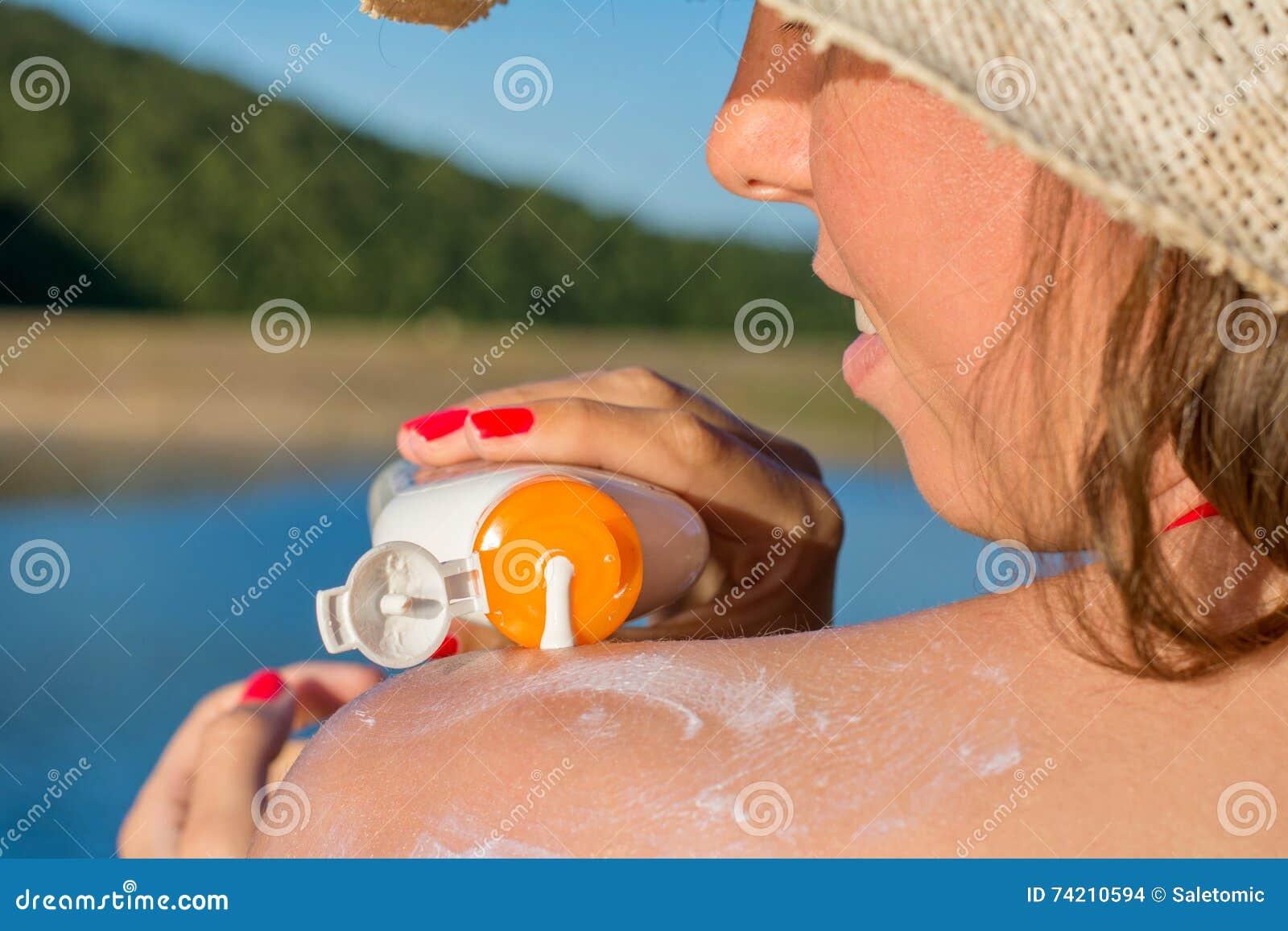 Mujer joven que pone la loción del sol el vacaciones de verano