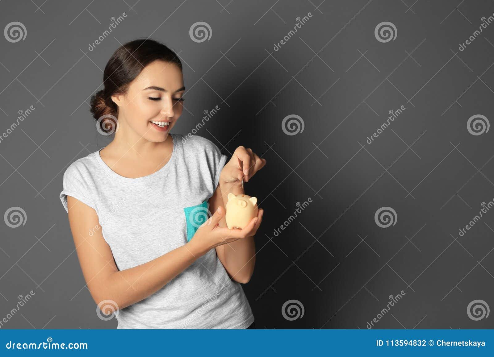 Mujer joven que pone la moneda en la hucha