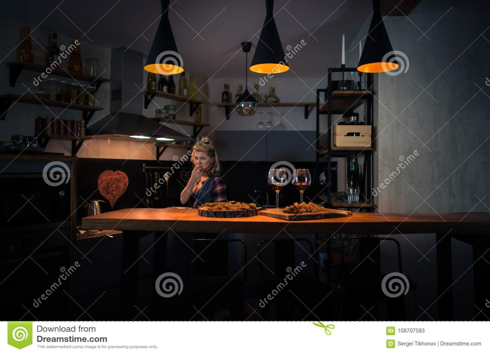 Mujer joven que prepara la cena en la cocina casera moderna