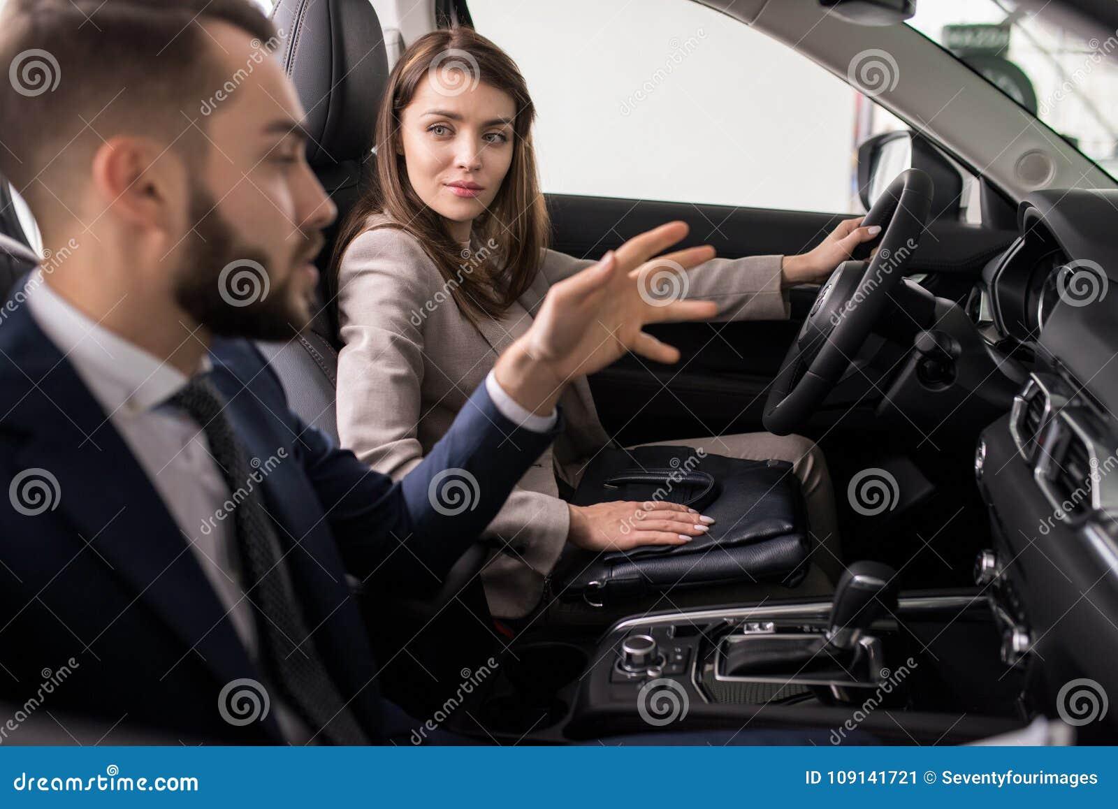 Mujer joven que prueba el nuevo coche en la sala de exposición