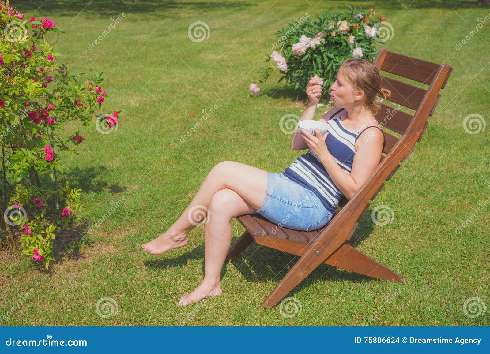 Mujer joven que relaja y que come el helado