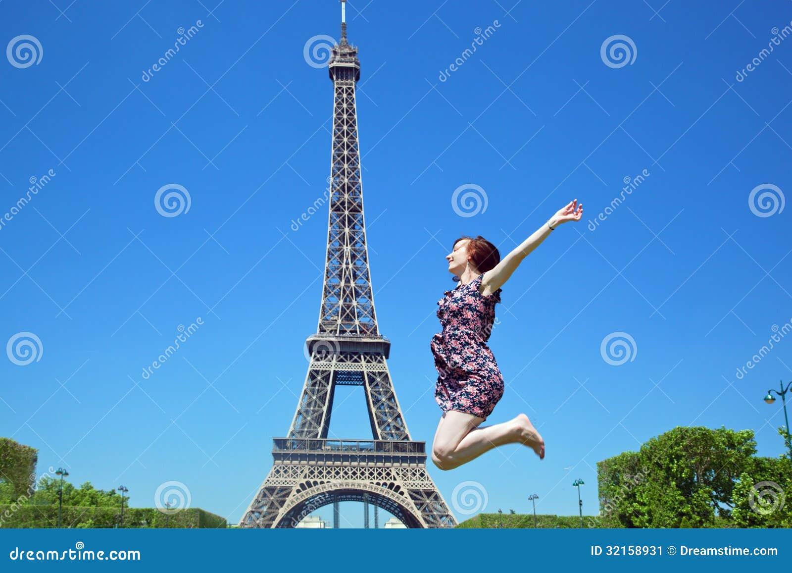 Mujer joven que salta contra torre Eiffel