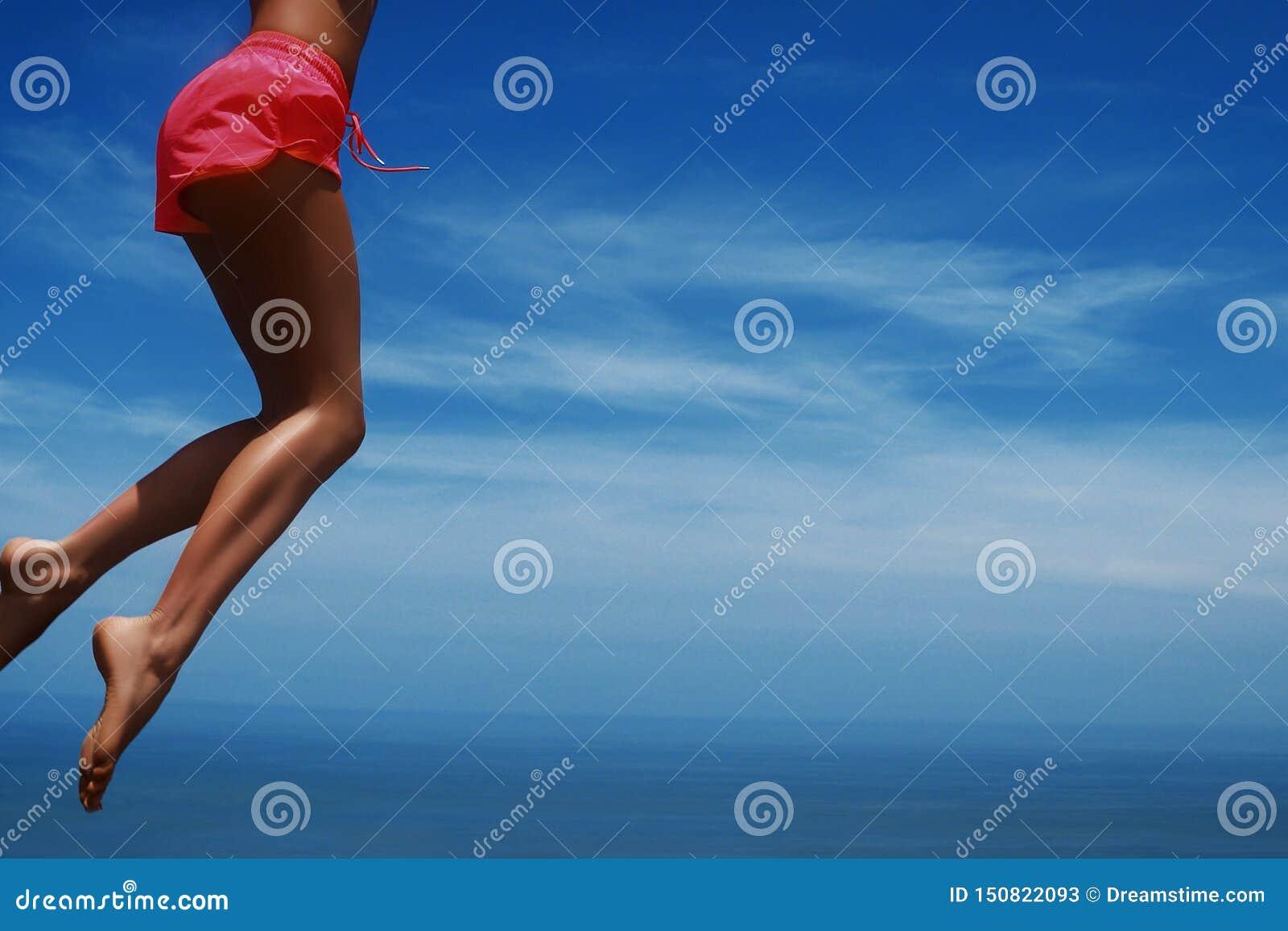 Mujer joven que salta en la playa tropical Cielo azul y piernas delgadas