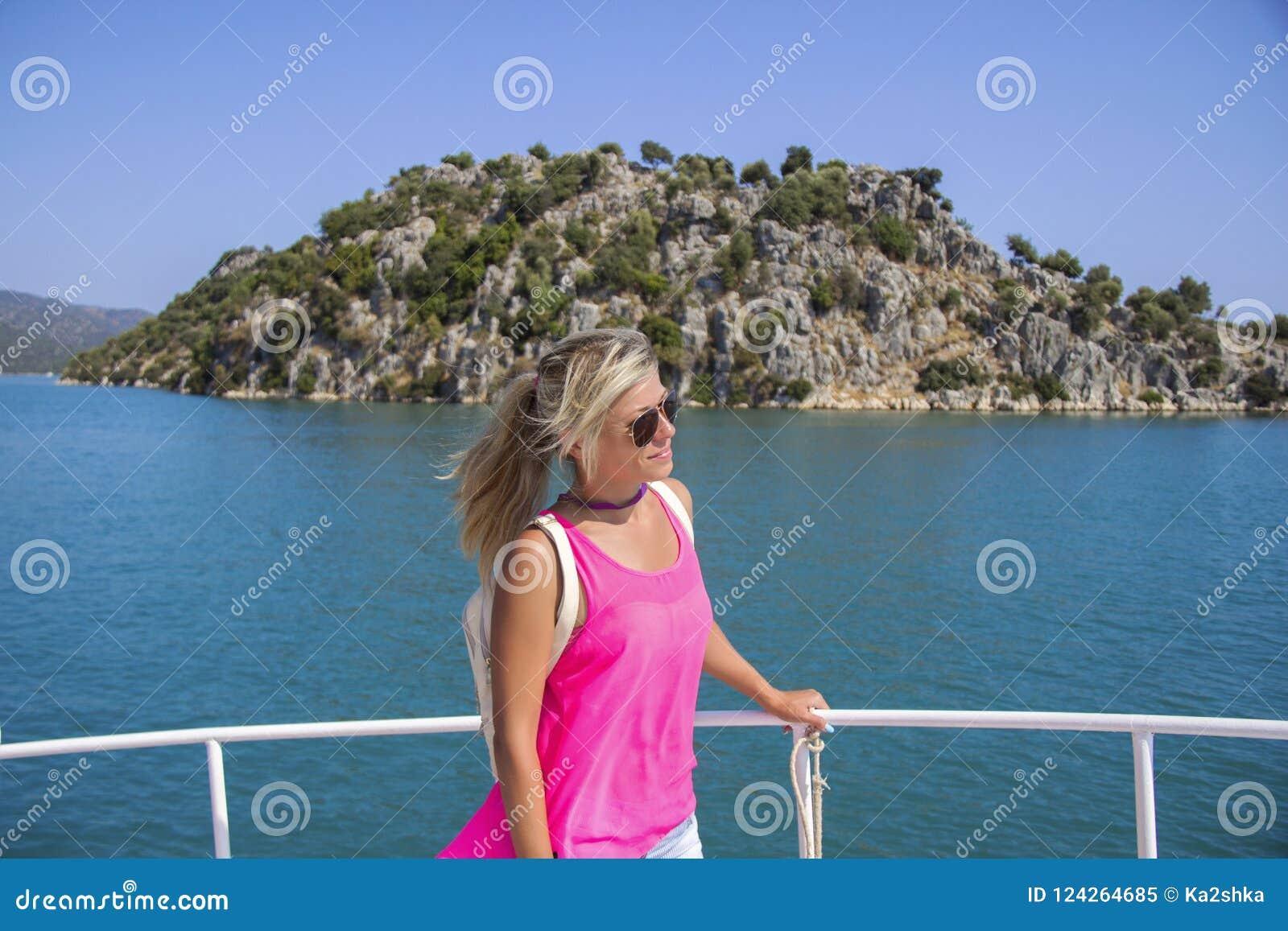 Mujer joven que se coloca en el yate en el día soleado y que mira a un mar