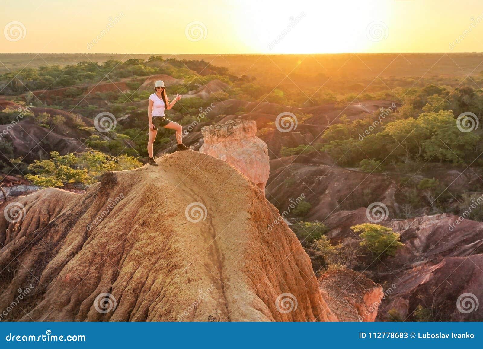 Mujer joven que se coloca encima de la colina, señalando en el sol
