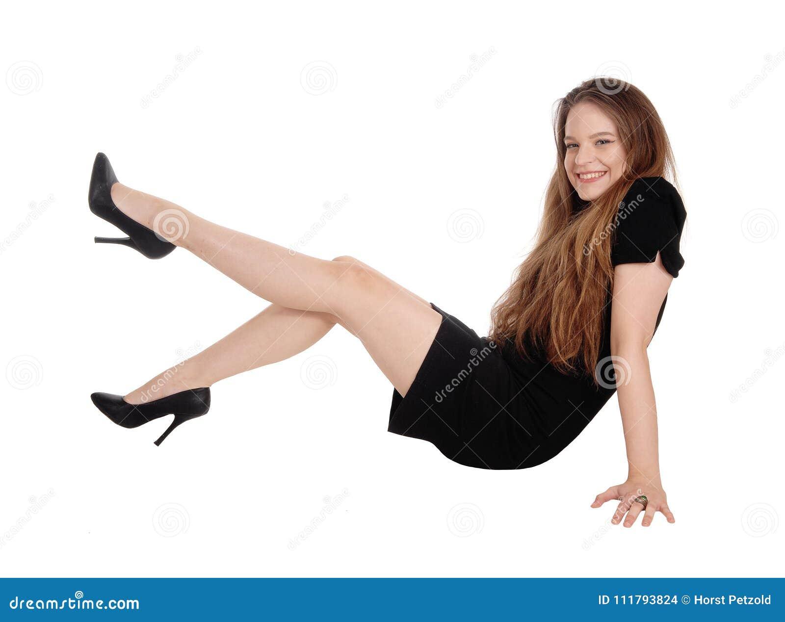 Mujer joven que se incorpora en el piso, piernas