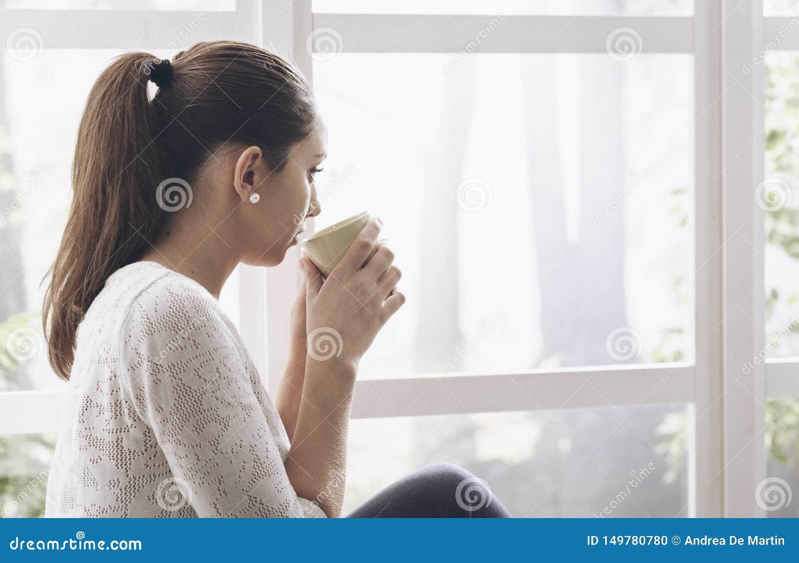 Mujer joven que se sienta al lado de la ventana y que mira lejos