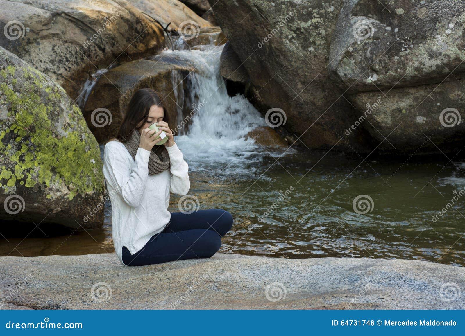 Mujer joven que se sienta cerca de la cascada y del té de consumición, surroun