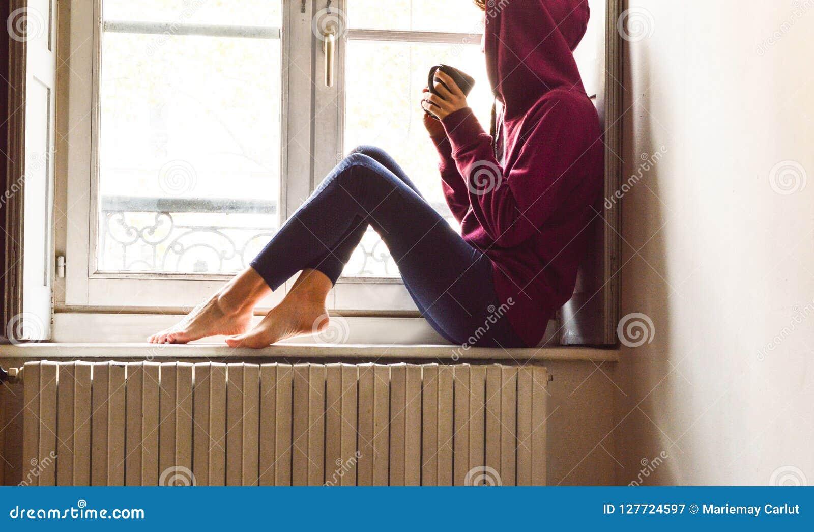 Mujer joven que se sienta cerca de la ventana que mira el café de consumición exterior en un humor nostálgico
