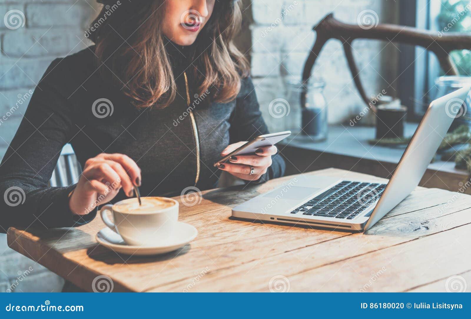 Mujer joven que se sienta en cafetería en la tabla de madera, el café de consumición y usando smartphone En la tabla es el ordena