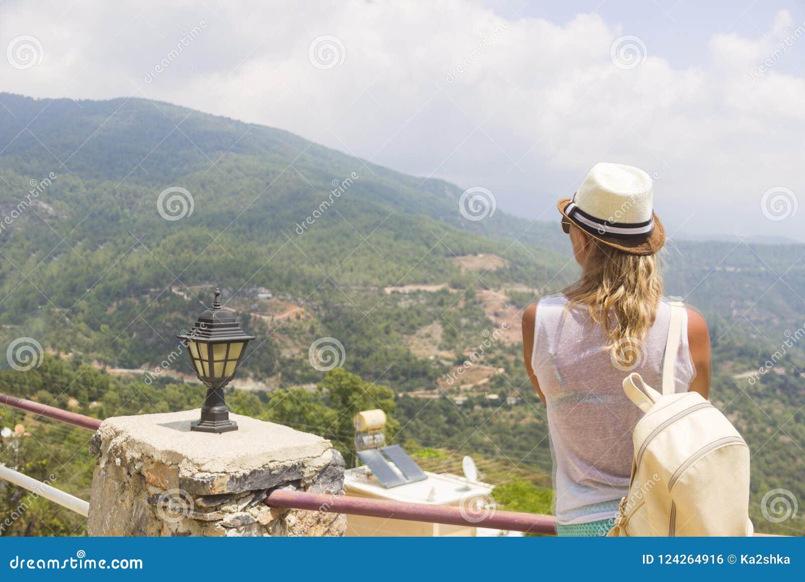 Mujer joven que se sienta en el borde del acantilado que mira sobre la vista expansiva de llanos y de montañas