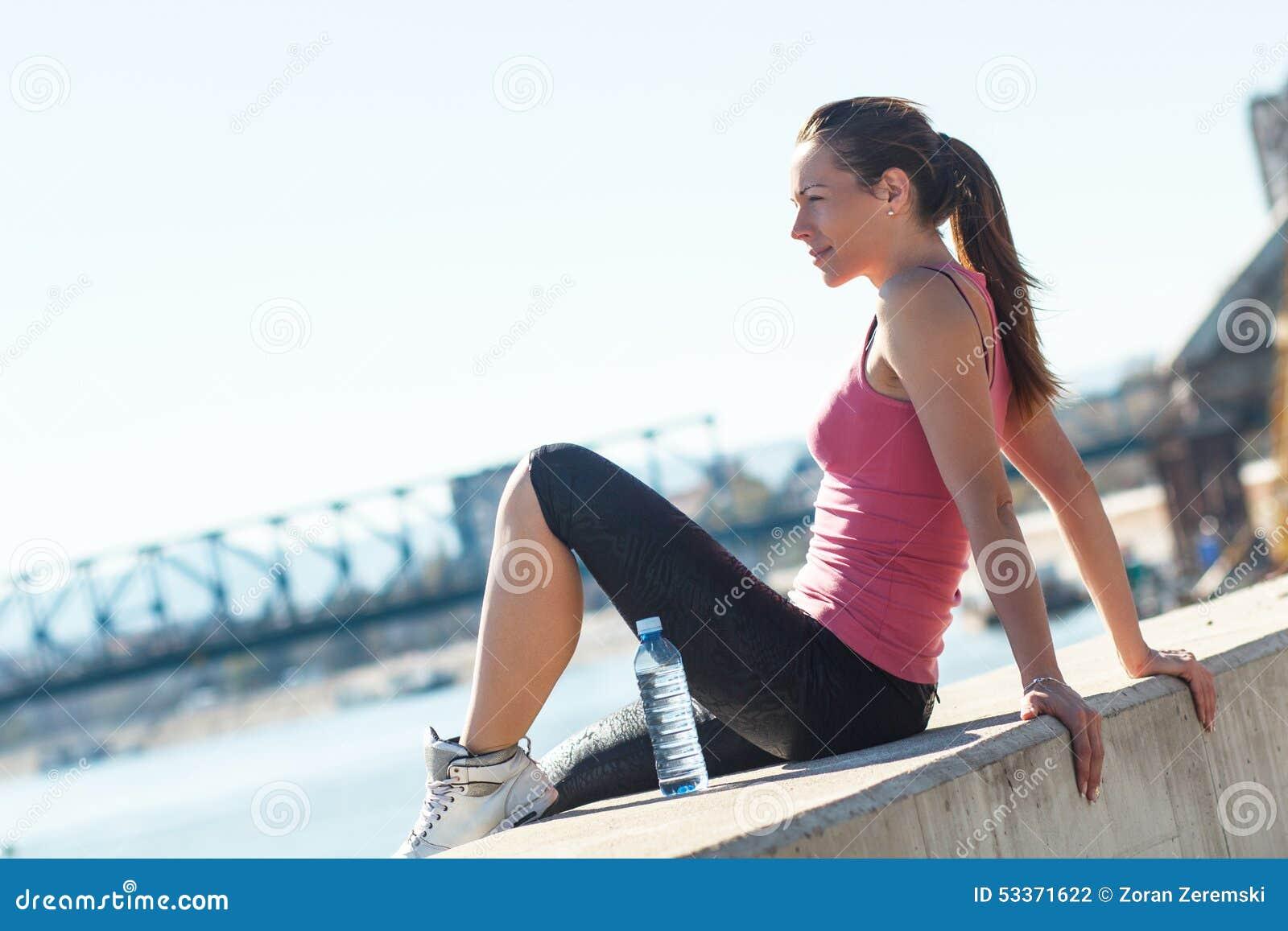 Mujer joven que se sienta en el riverbank
