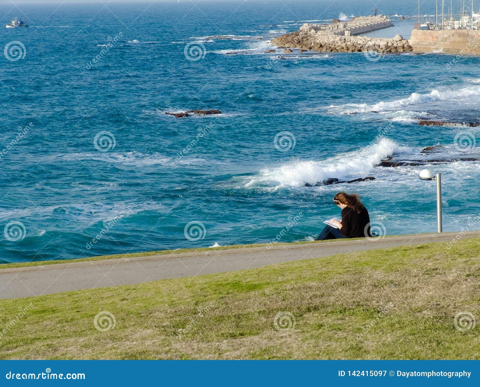Mujer joven que se sienta en la hierba verde en el parque, lectura, supervisando una vista del océano y del puerto de Jaffa