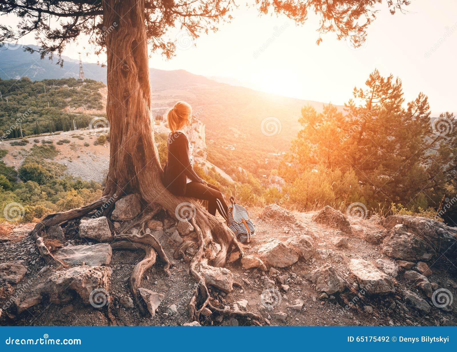 Mujer joven que se sienta en la montaña en la puesta del sol Paisaje del VERANO