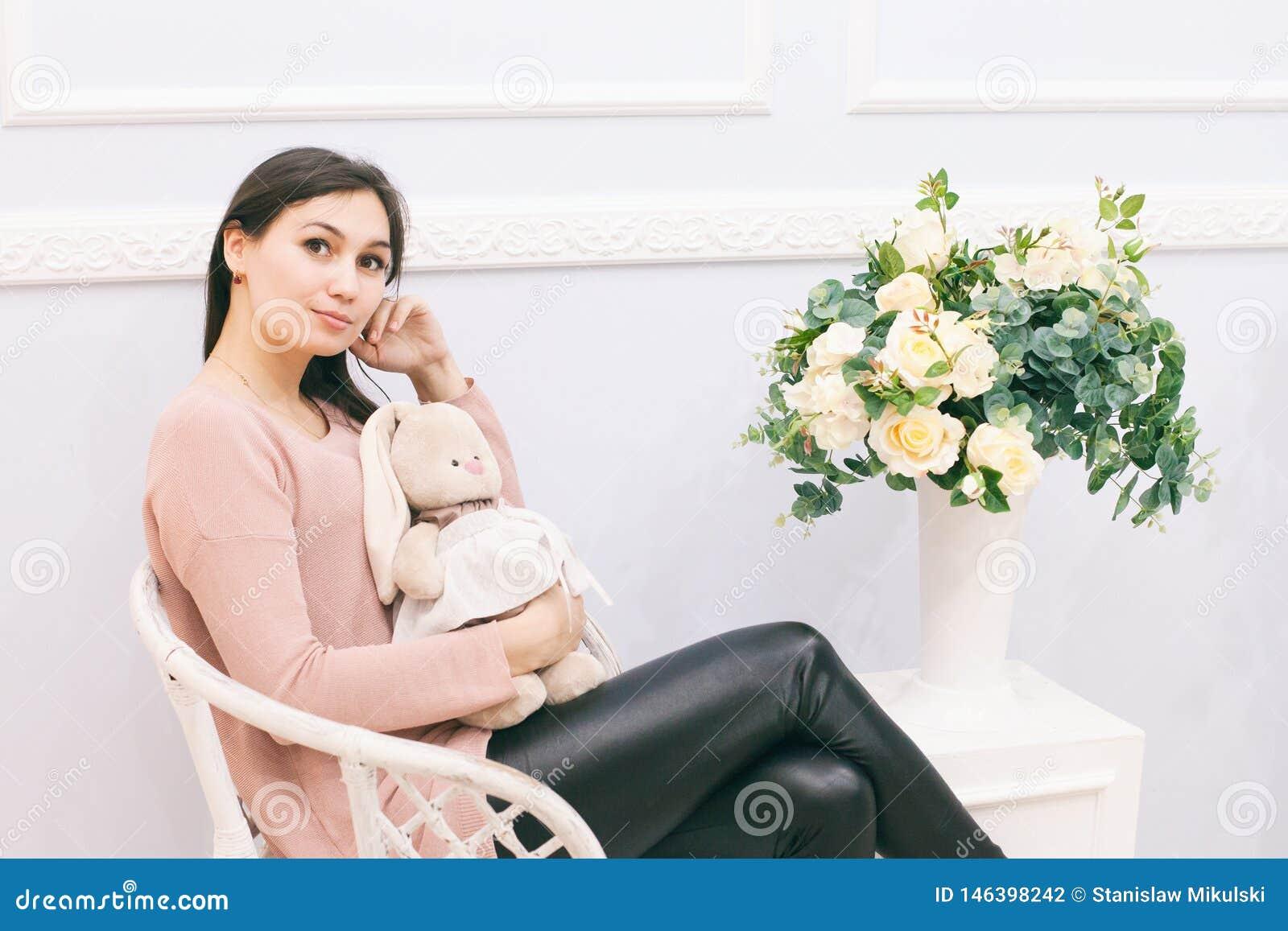 Mujer joven que se sienta en silla de mimbre en casa