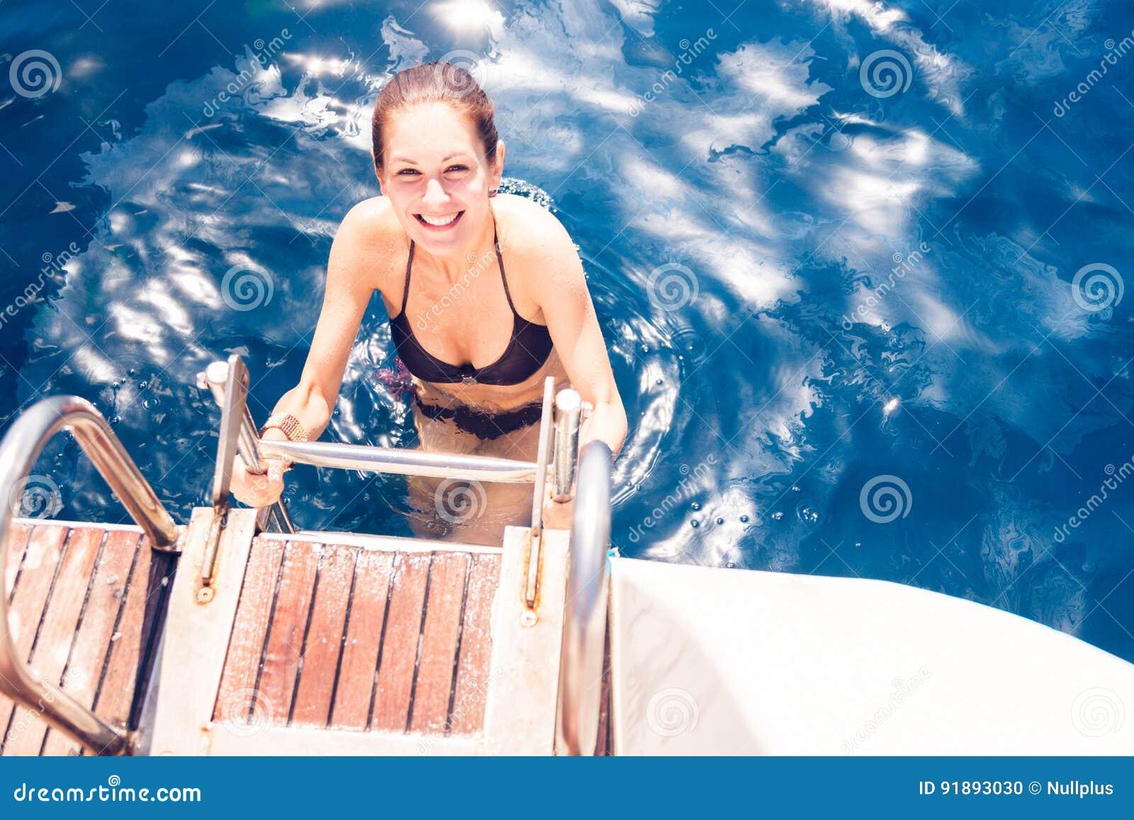 Mujer joven que sube fuera del mar