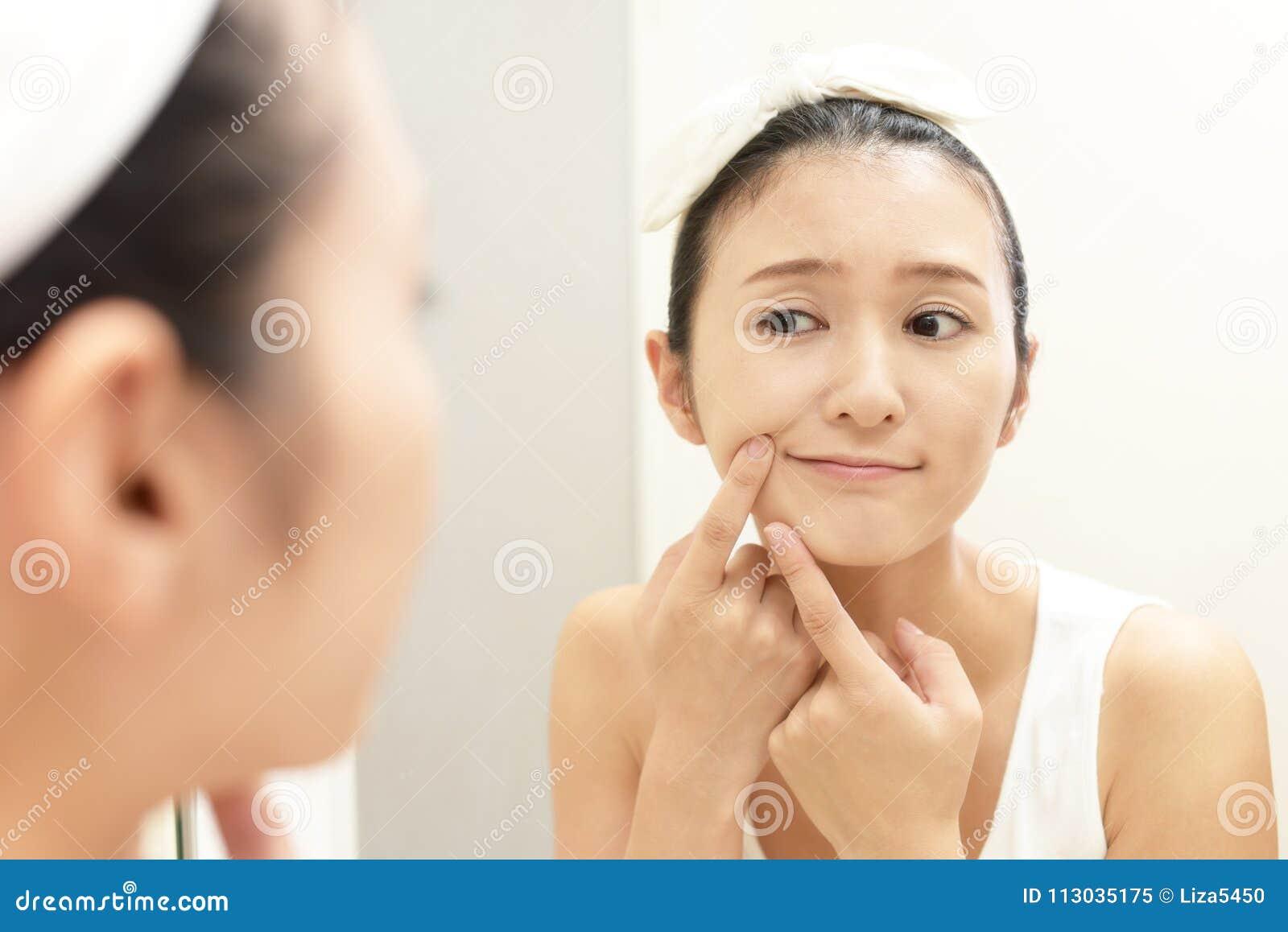 Mujer joven que tiene problemas de piel
