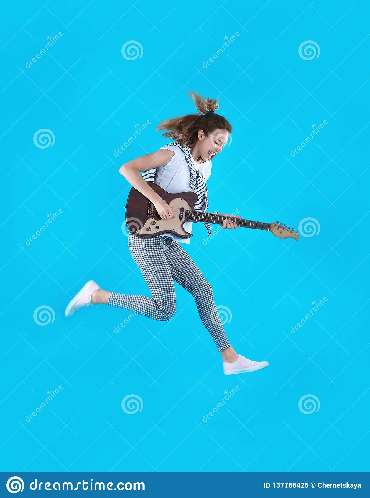 Mujer joven que toca la guitarra eléctrica