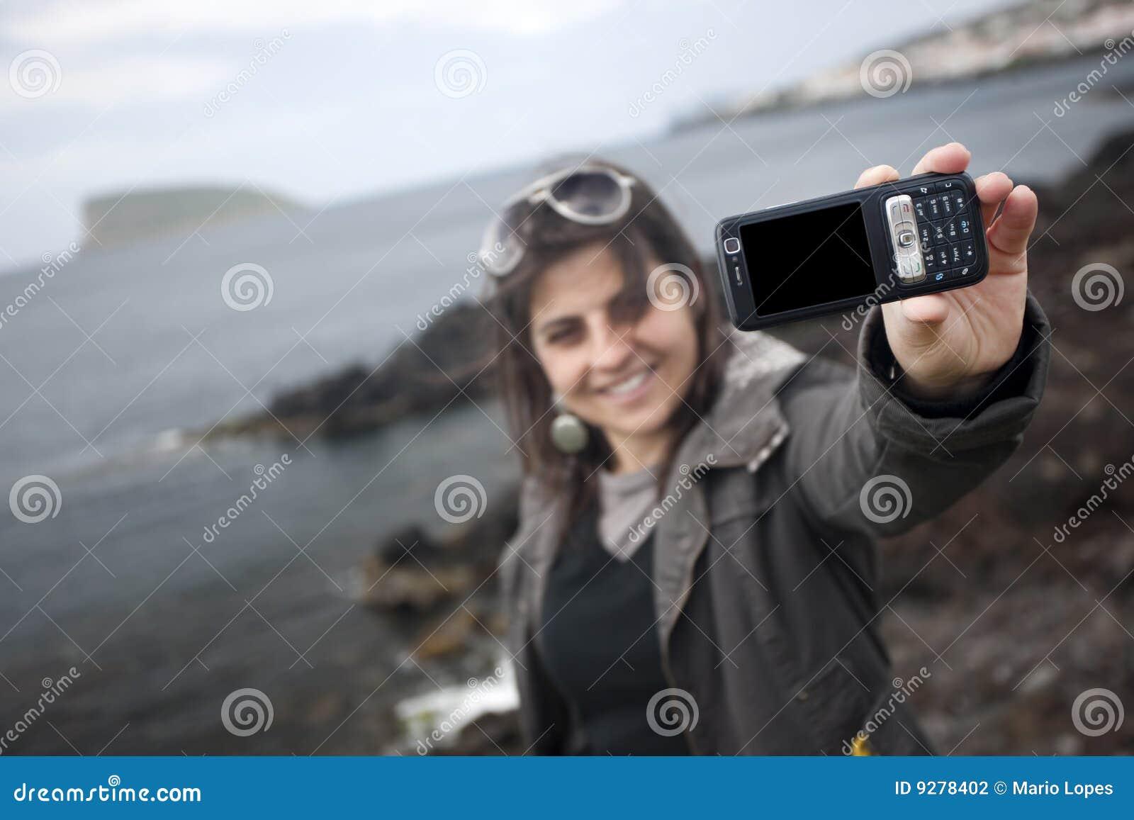 Mujer joven que toma el retrato de uno mismo con el teléfono móvil