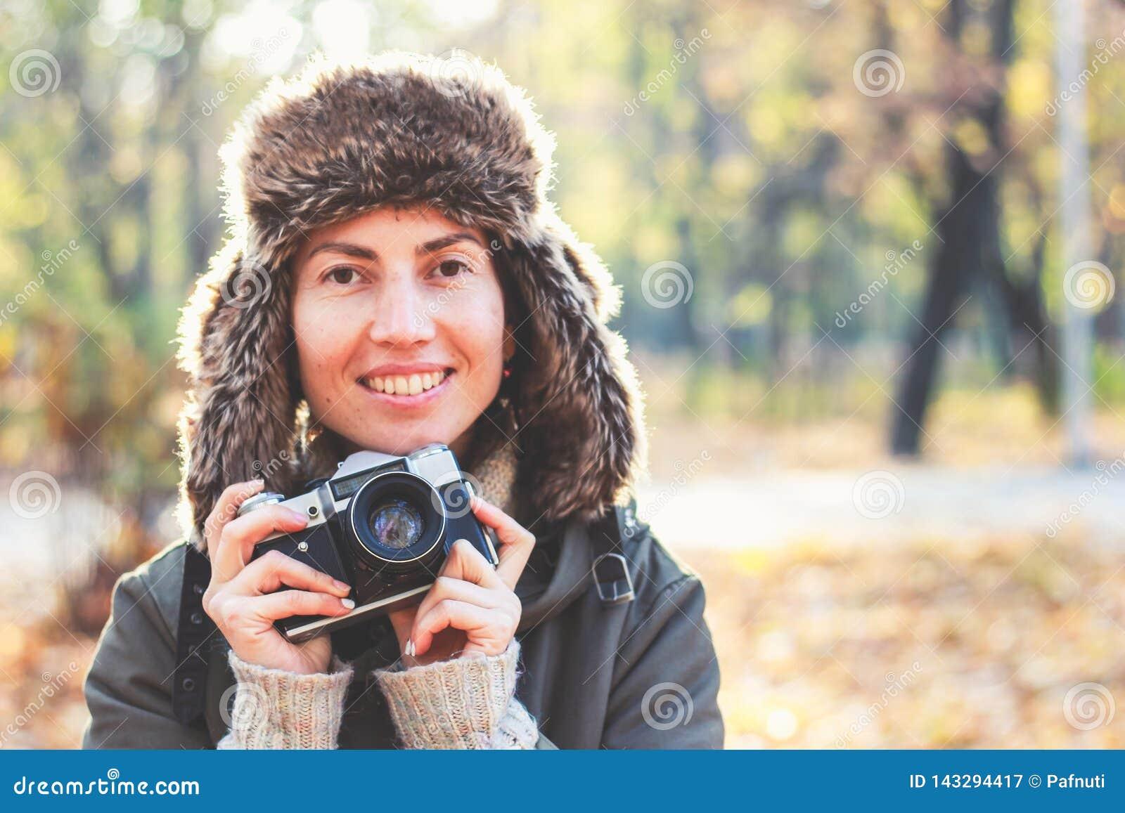 Mujer joven que toma imágenes en el parque del otoño