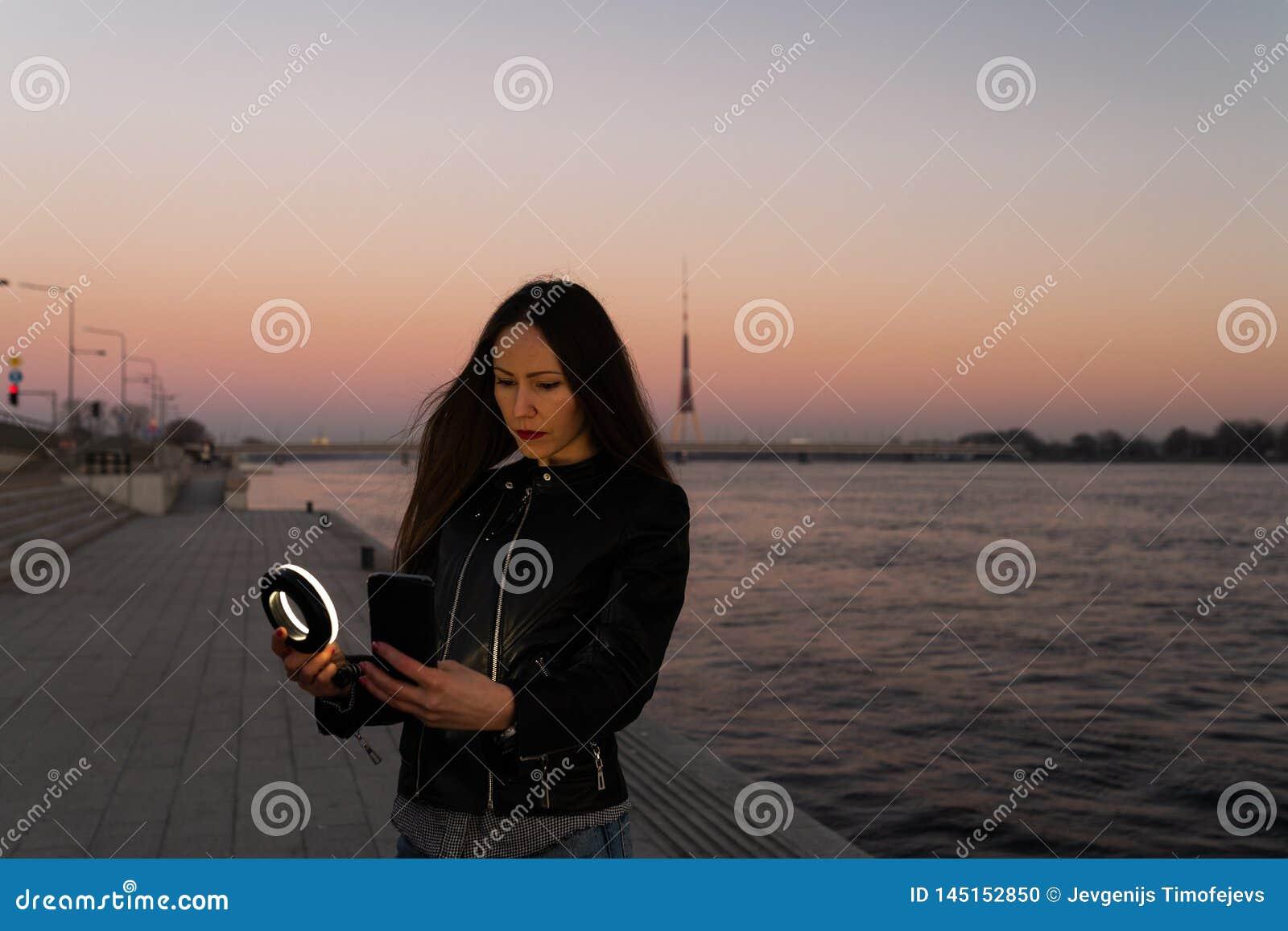 Mujer joven que toma un selfie usando un flash del anillo como luz del terraplén en una puesta del sol con una visión sobre Dau