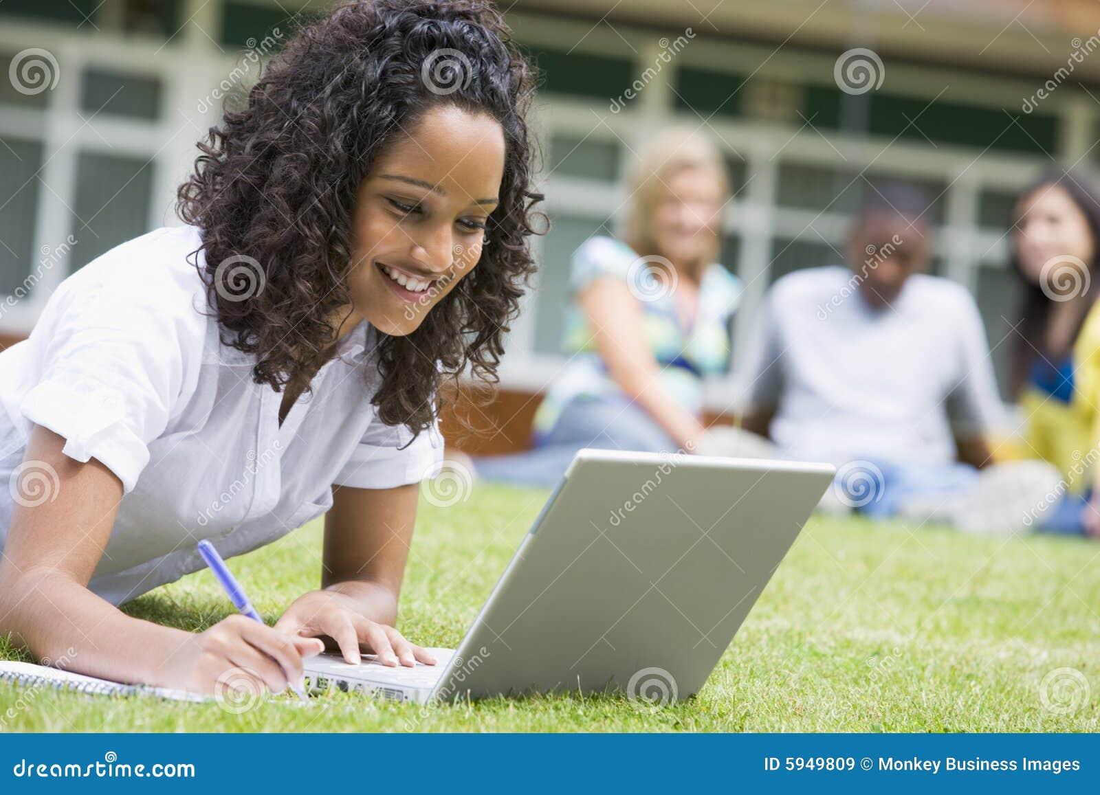Mujer joven que usa la computadora portátil en césped del campus