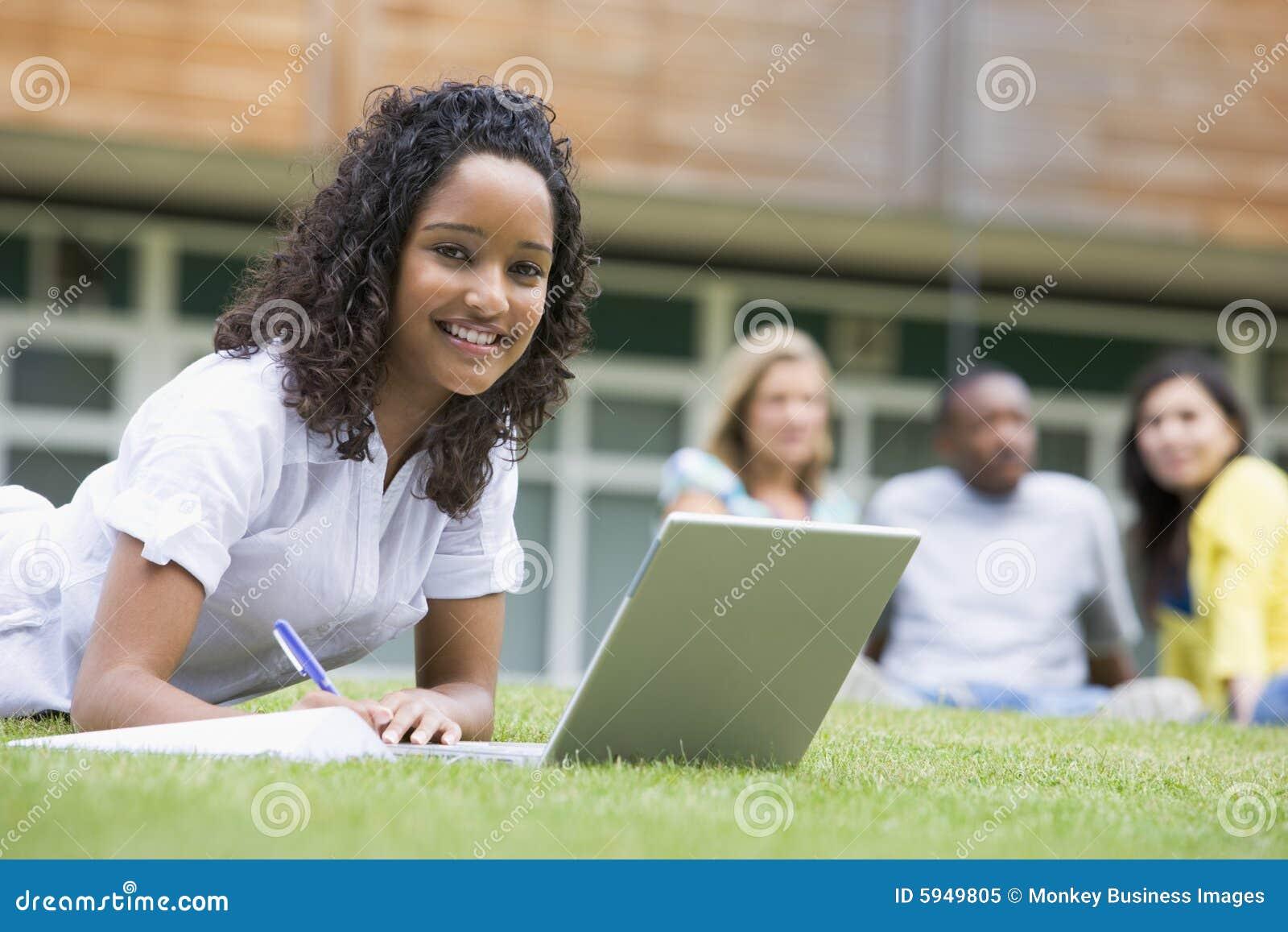 Mujer joven que usa la computadora portátil en campus