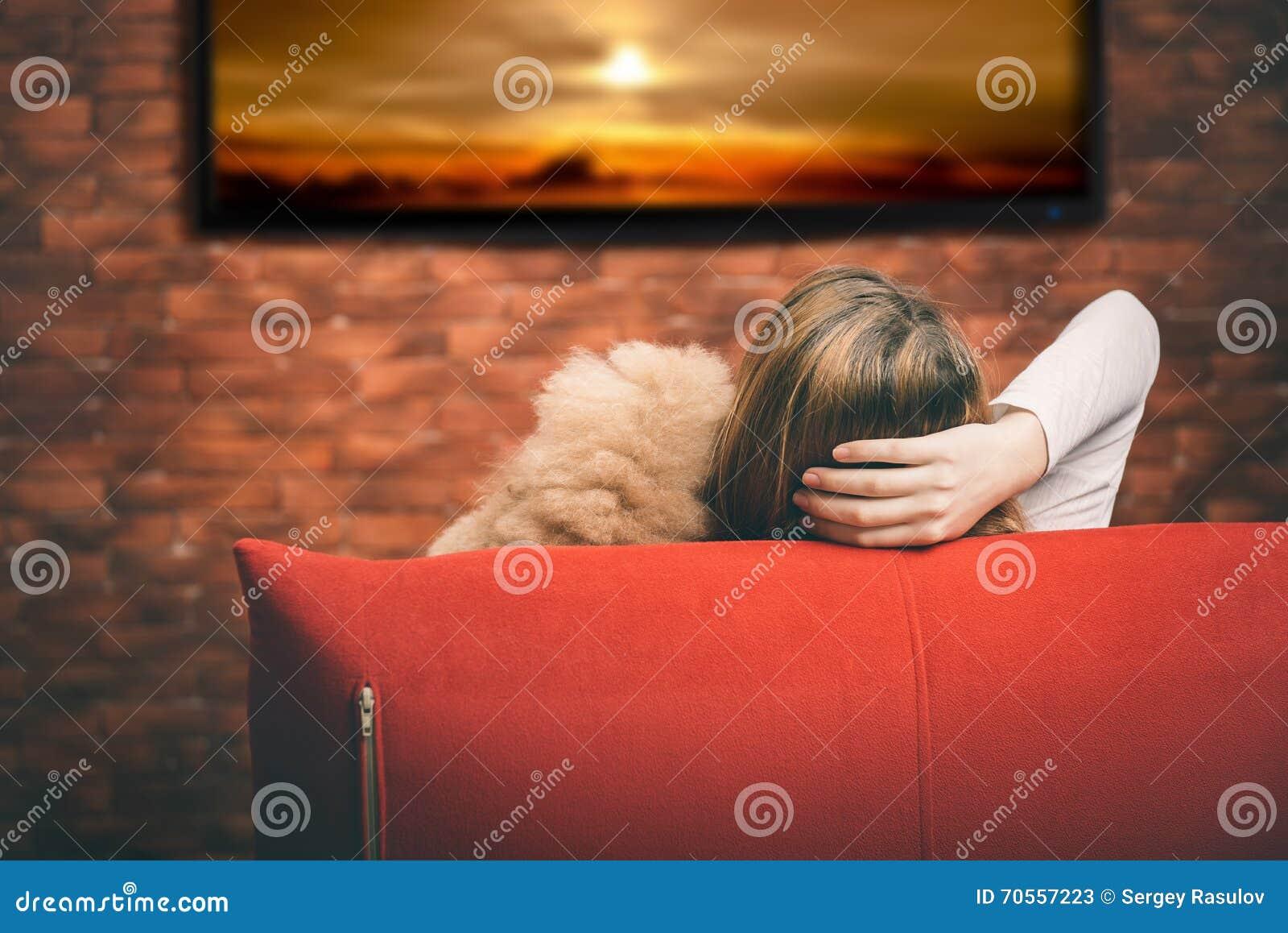Mujer joven que ve la TV elegante