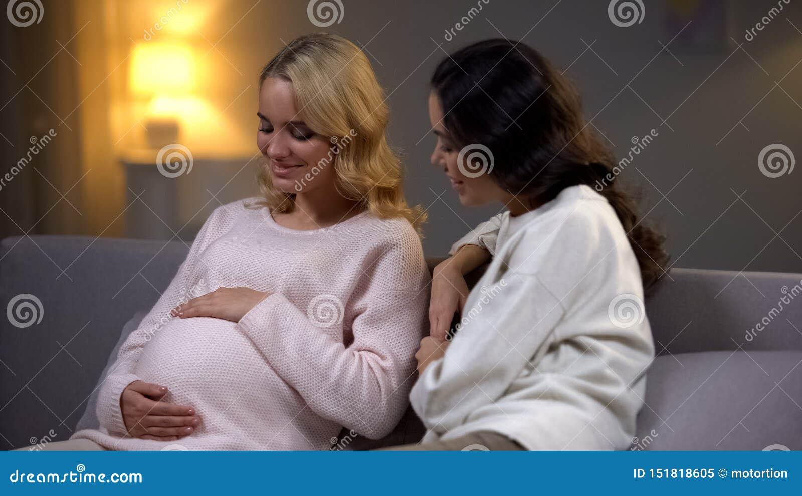 Mujer joven que visita a su amigo embarazada en casa, maternidad feliz, nueva vida