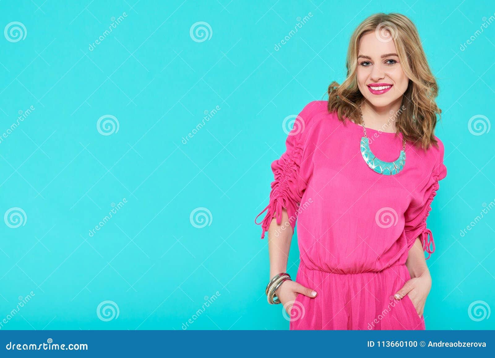 Mujer joven rubia atractiva en vestido de fiesta de moda y accesorios a juego Muchacha que presenta en un fondo azul en colores p